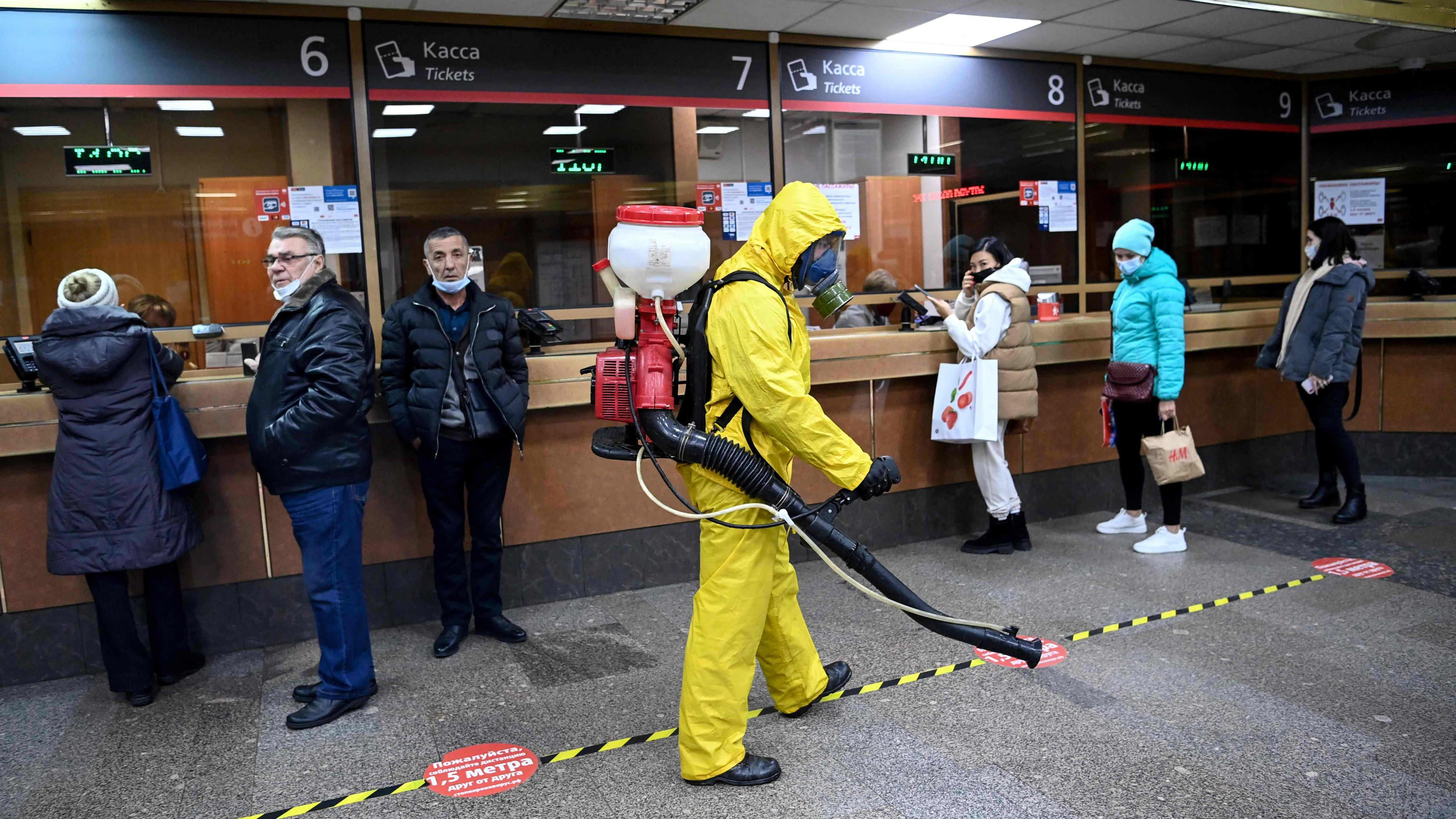 Suojapukuinen henkilö definsioimassa Moskovan rautatieasemalla.
