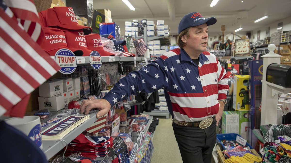 Jari Mäki Trump-rekvisiittahyllyn edessä myymälässään