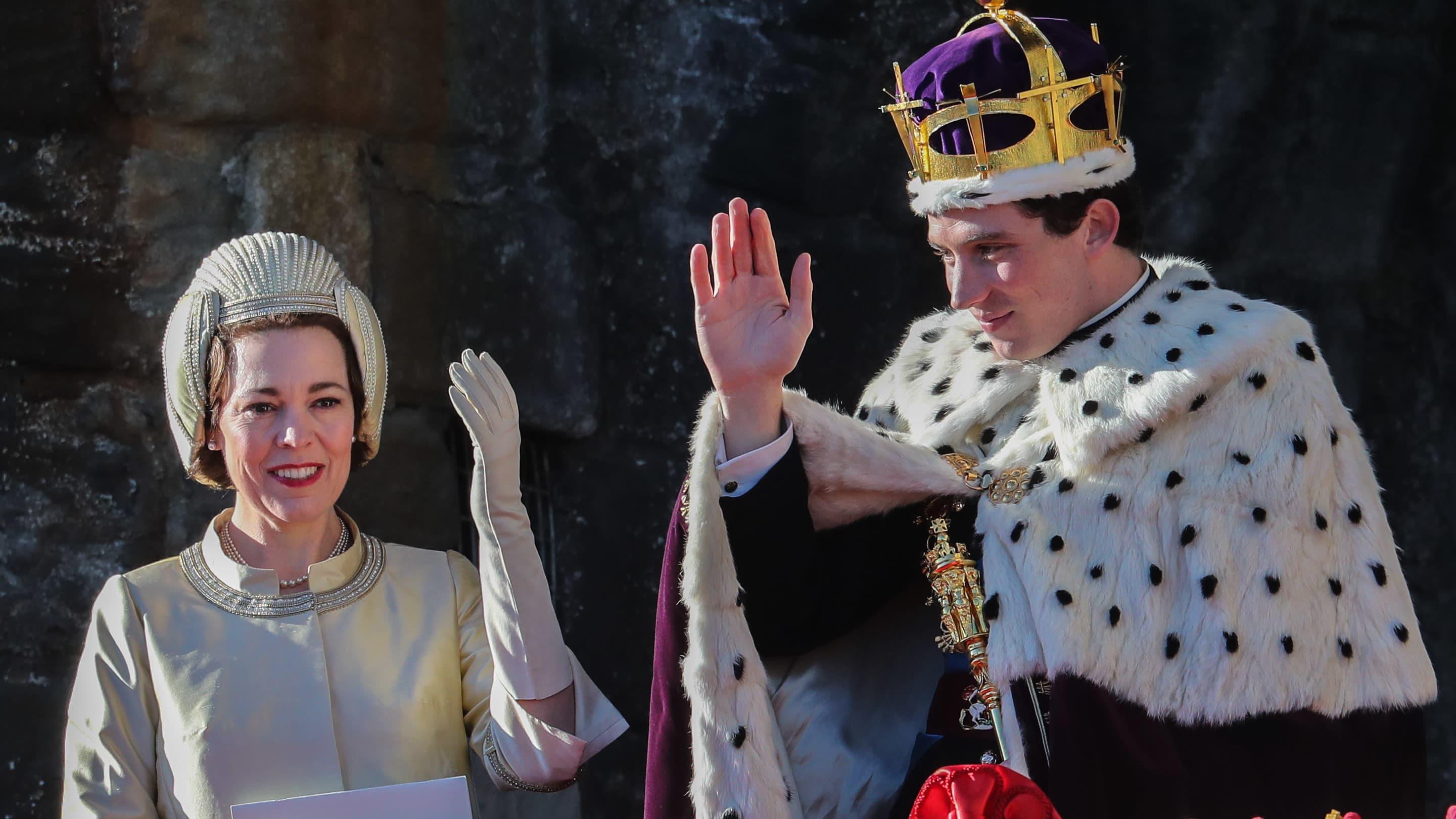 Drottning Elizabeth (Olivia Colman) och prins Charles (Josh O'Connor) vinkar på en balkong, bilden är tagen under inspelningen av serien The Crown.