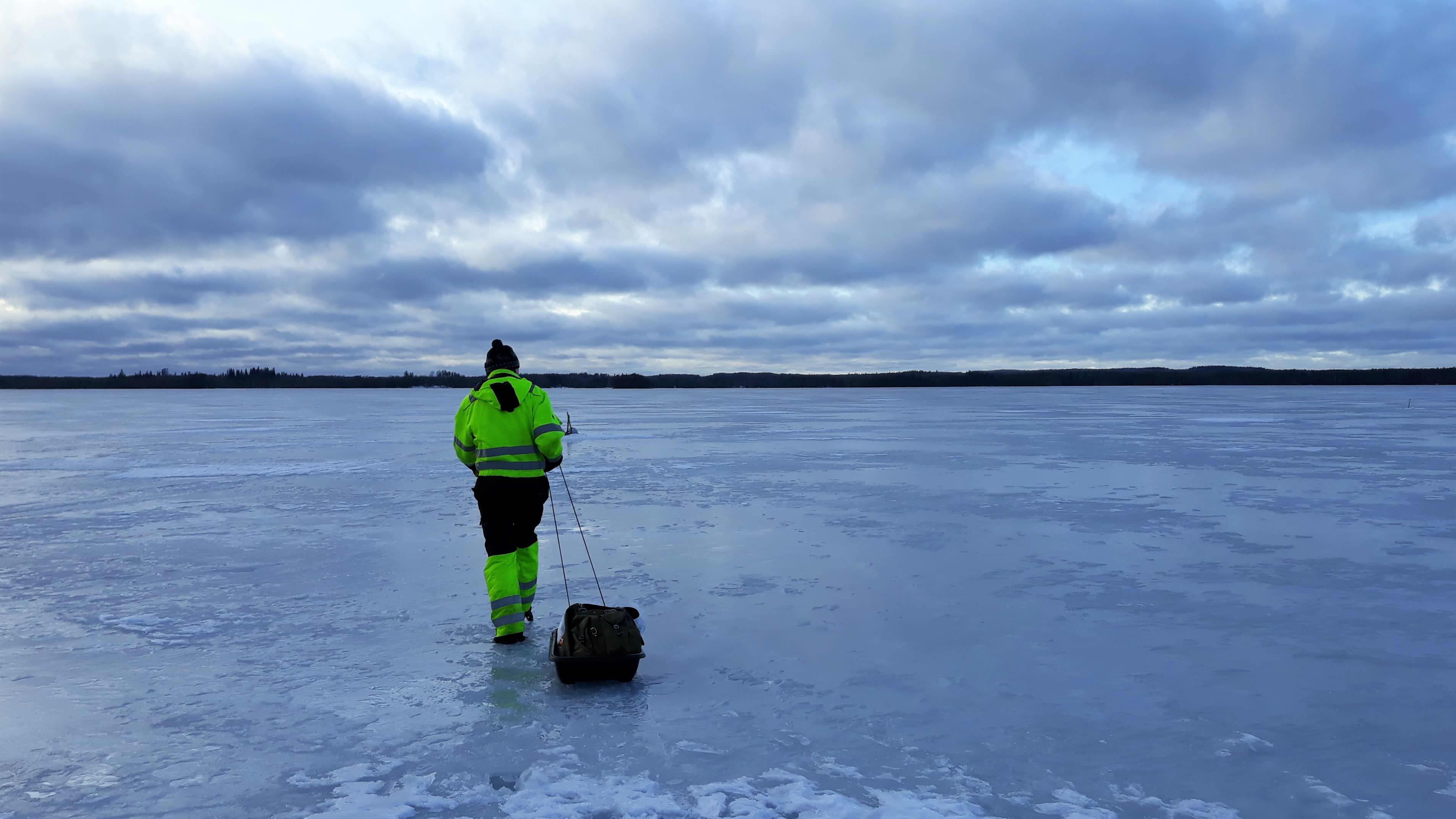 Kalastaja vetää ahkiota järven jäällä.