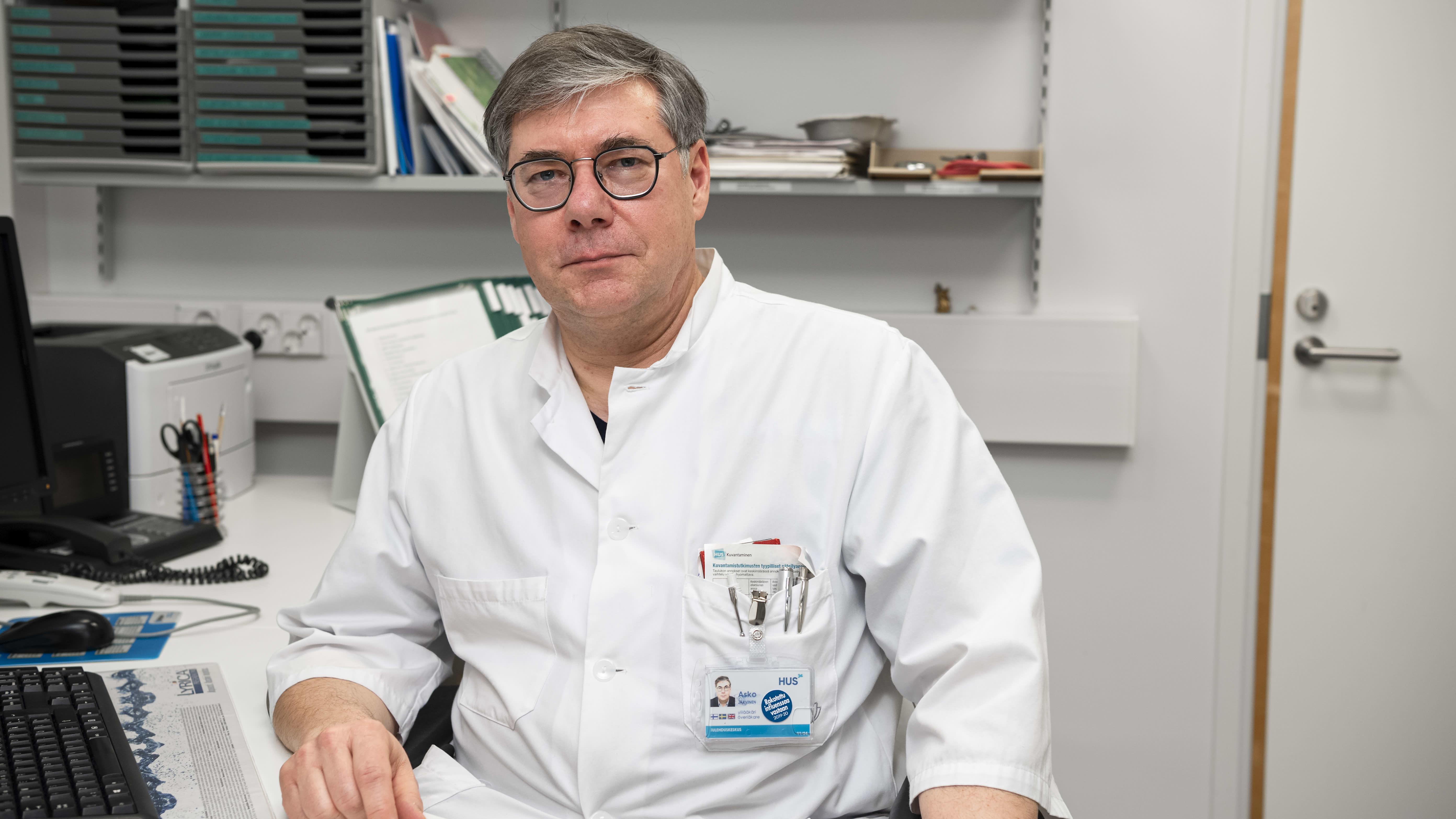 Asko Järvinen sitter inne på sitt arbetskontor iklädd läkarjacka.