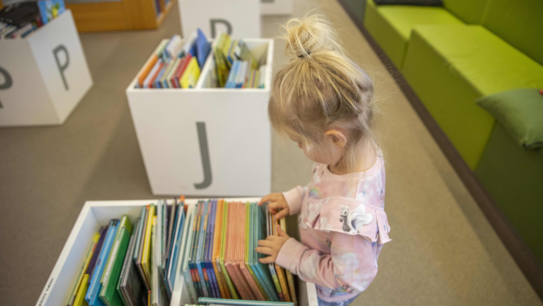 Lapsi tutkii kirjastossa  kirjoja.