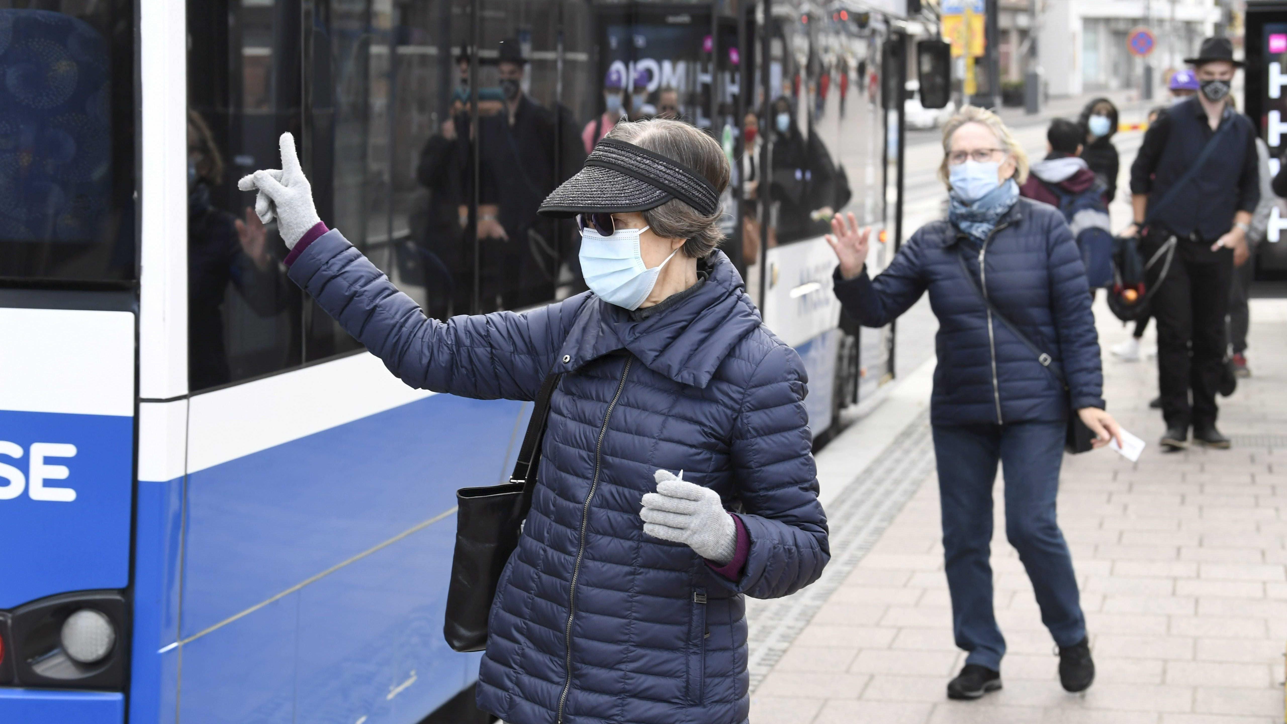 Matkustajat maskit kasvoillaan odottavat bussia Ratinan edustalla Tampereella 2. syyskuuta 2021.