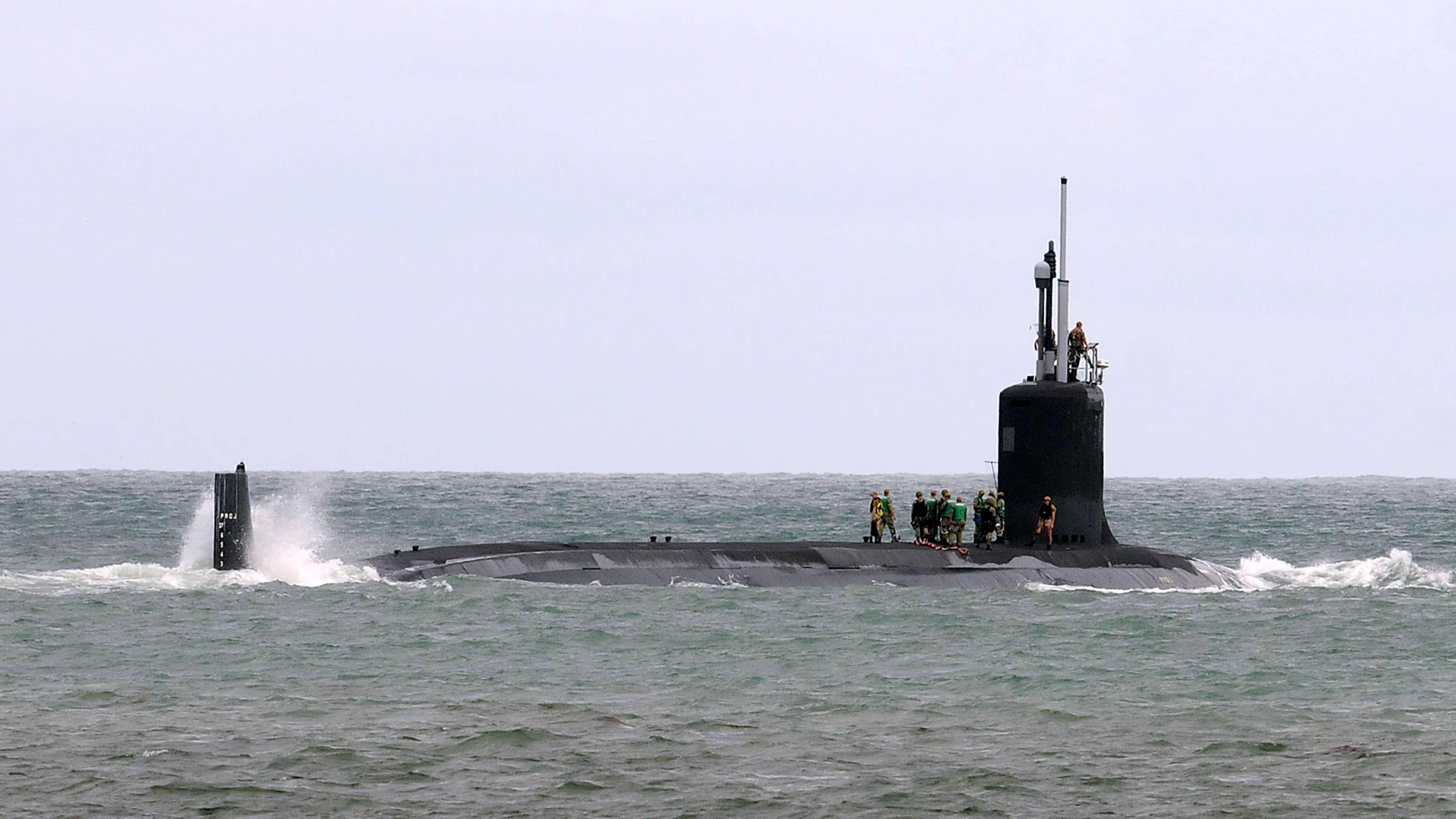 Iso sukellusvene vesillä, puoliksi pinnalla. Veneen päällä seisoo ihmisiä.