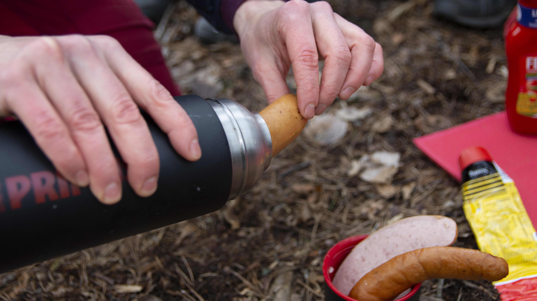 Esikypsytettyjä makkaranpaloja otetaan termospullosta, jossa myös kuumaa vettä. Koronapandemian aikana yleisiä grillauspaikkoja on syytä välttää.