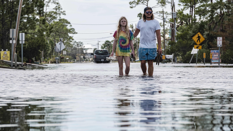 Mies ja nainen kävelevät tulvivalla kadulla.