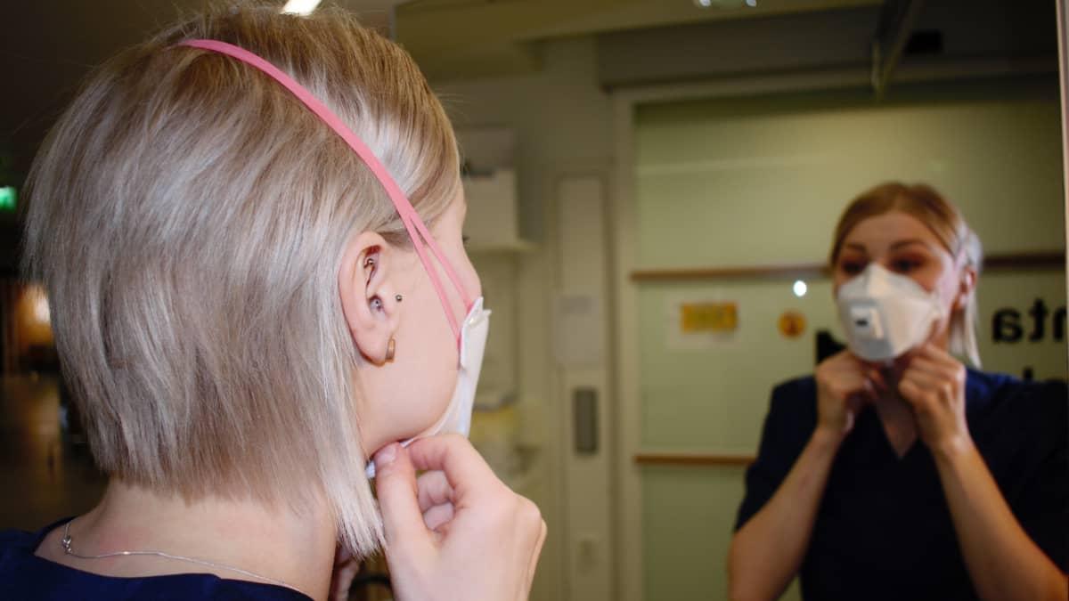Sairaanhoitaja Heini Laukkanen laittaa maskia kasvoilleen.