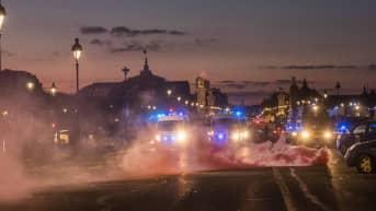 Kyynelkaasua leijailee poliisin hälytysajoneuvojen valojen edessä.