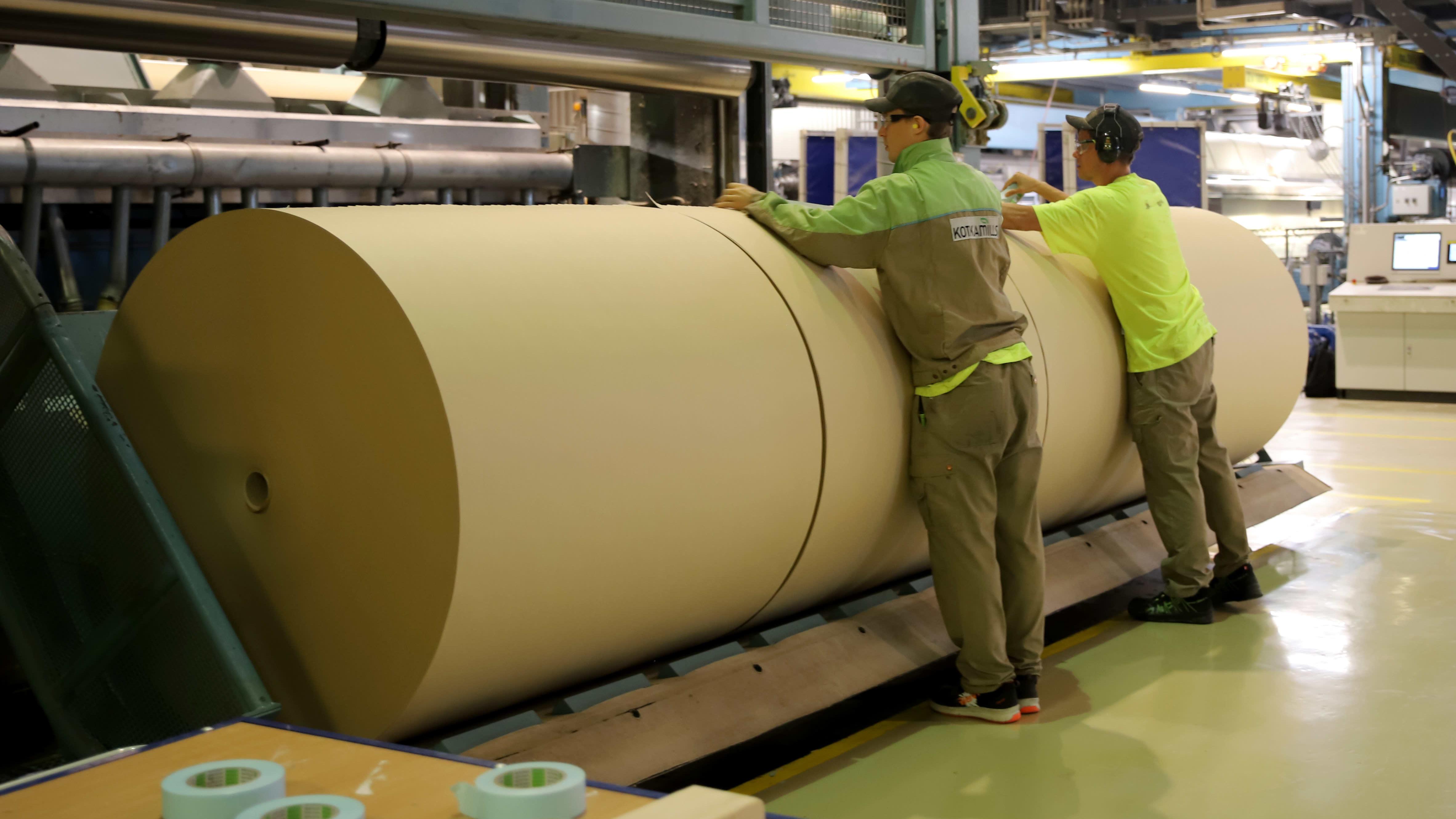 työntekijät teippaavat laminaattipaperirullia Kotkamillsin tehtaassa
