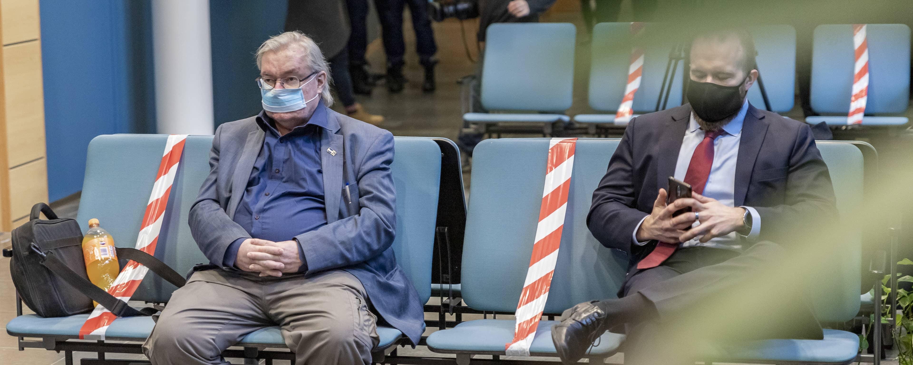 Pekka Kataja istuu oikeussalin aulassa asianajajansa kanssa.