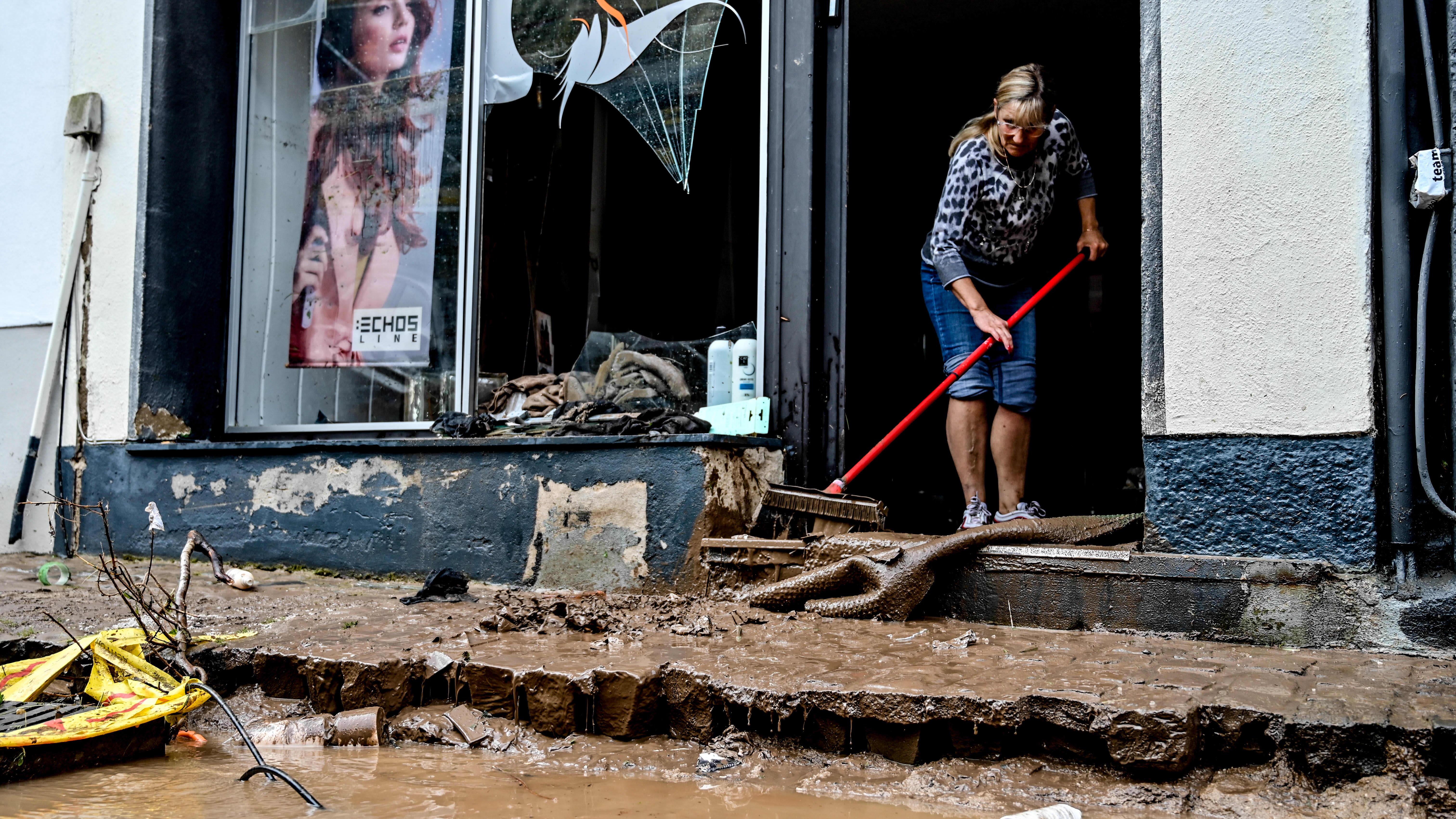 Nainen siivoaa tulvan tuhoaman liikkeen ovella.