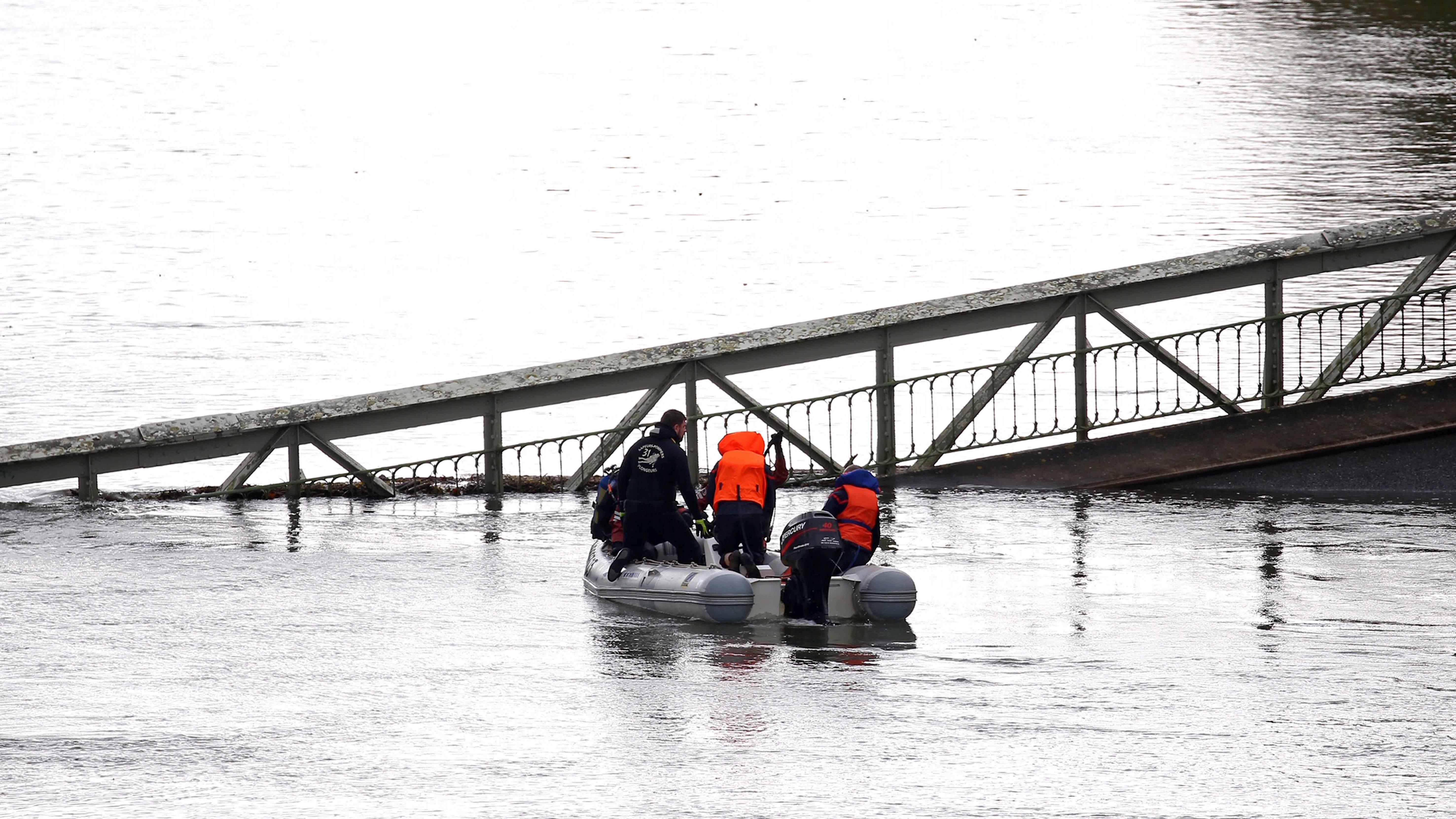 Pelastustyöntekijät kumiveneessä joessa olevan sillan luona.