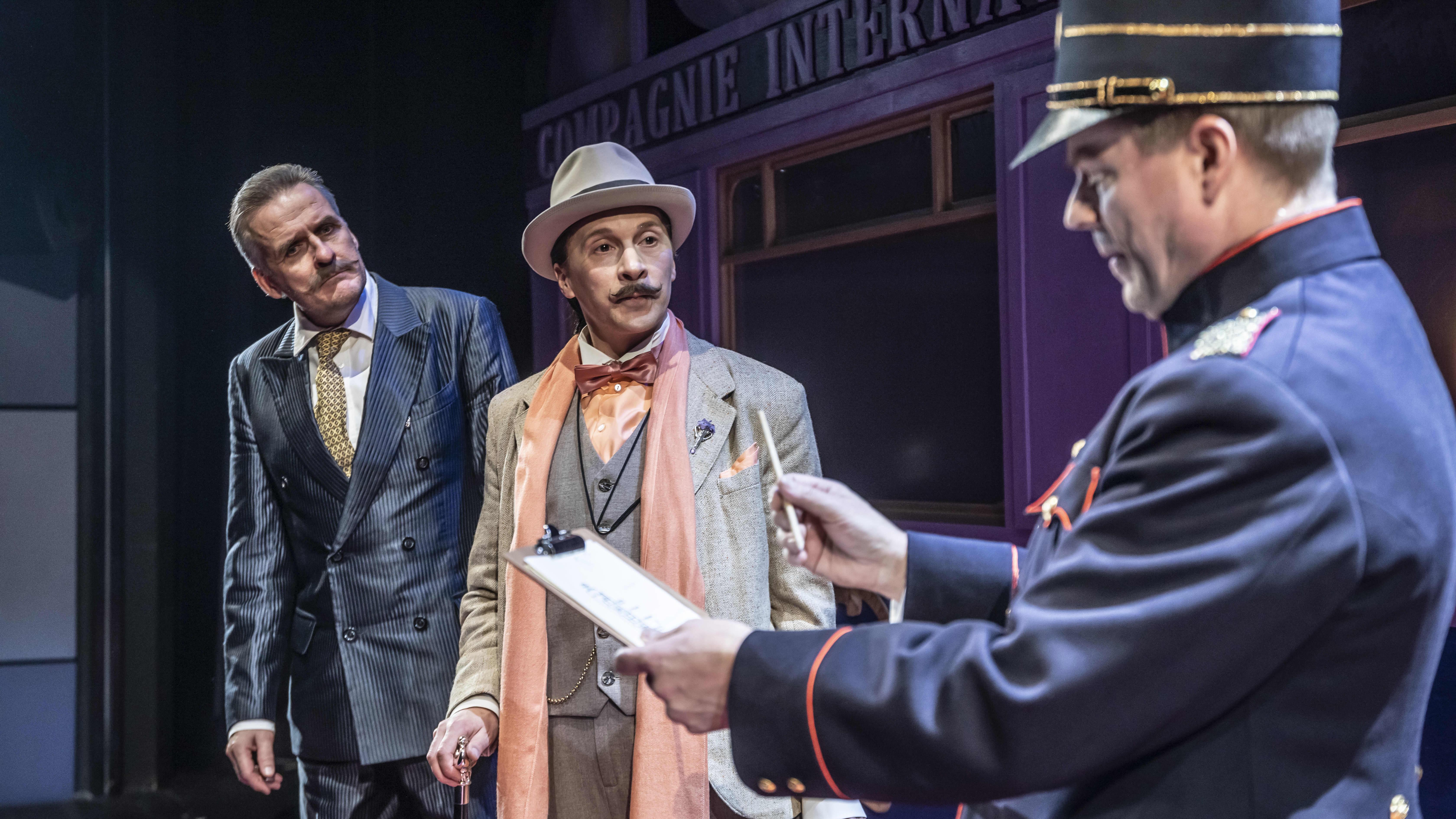 Kolme miestä junavaunussa: konduktööri ja kaksi matkustajaa.