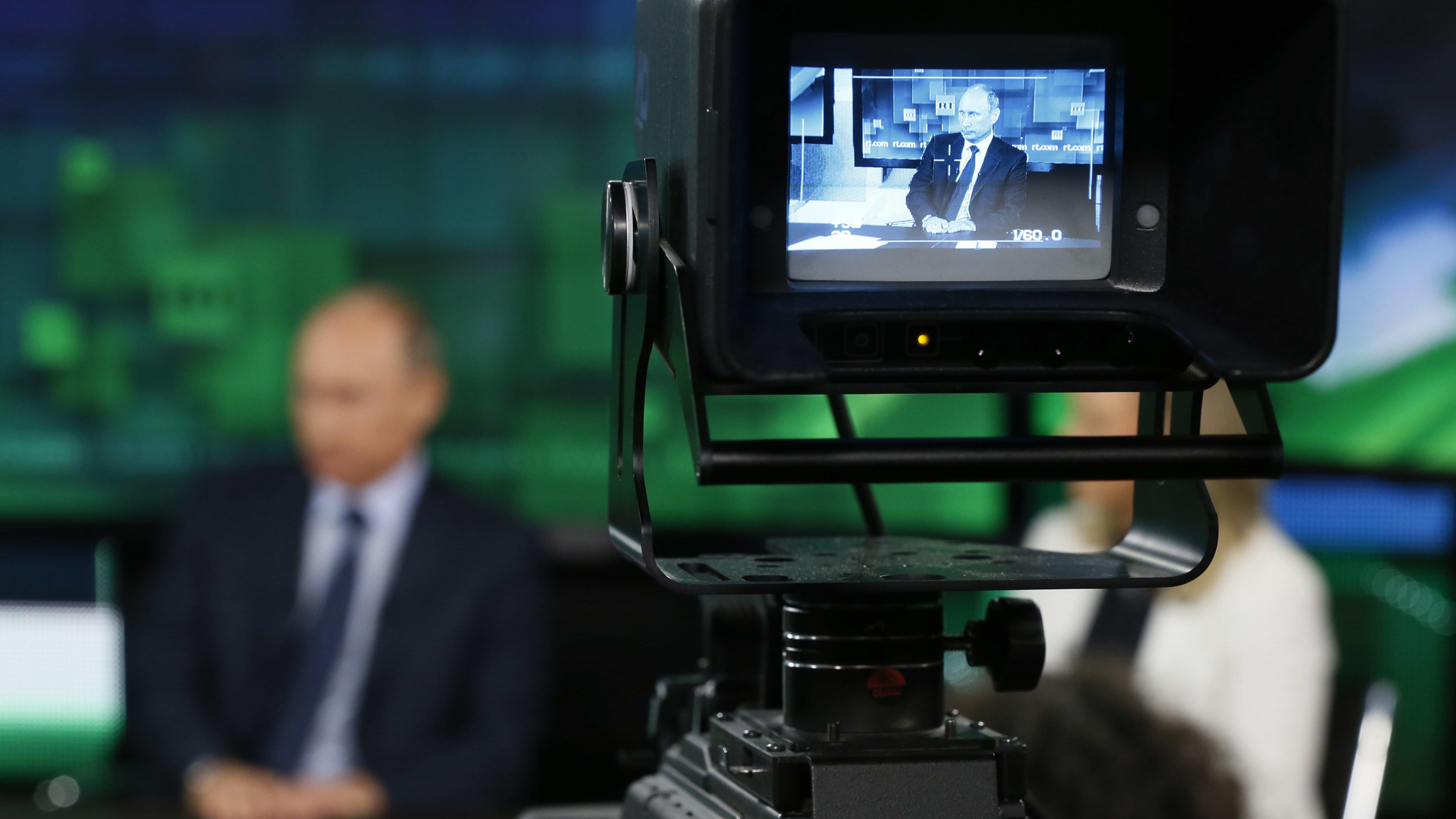 Presidentti Vladimir Putin näkyy häilyvänä kameran taustalla, RT-kanavan kuvaukset käynnissä.
