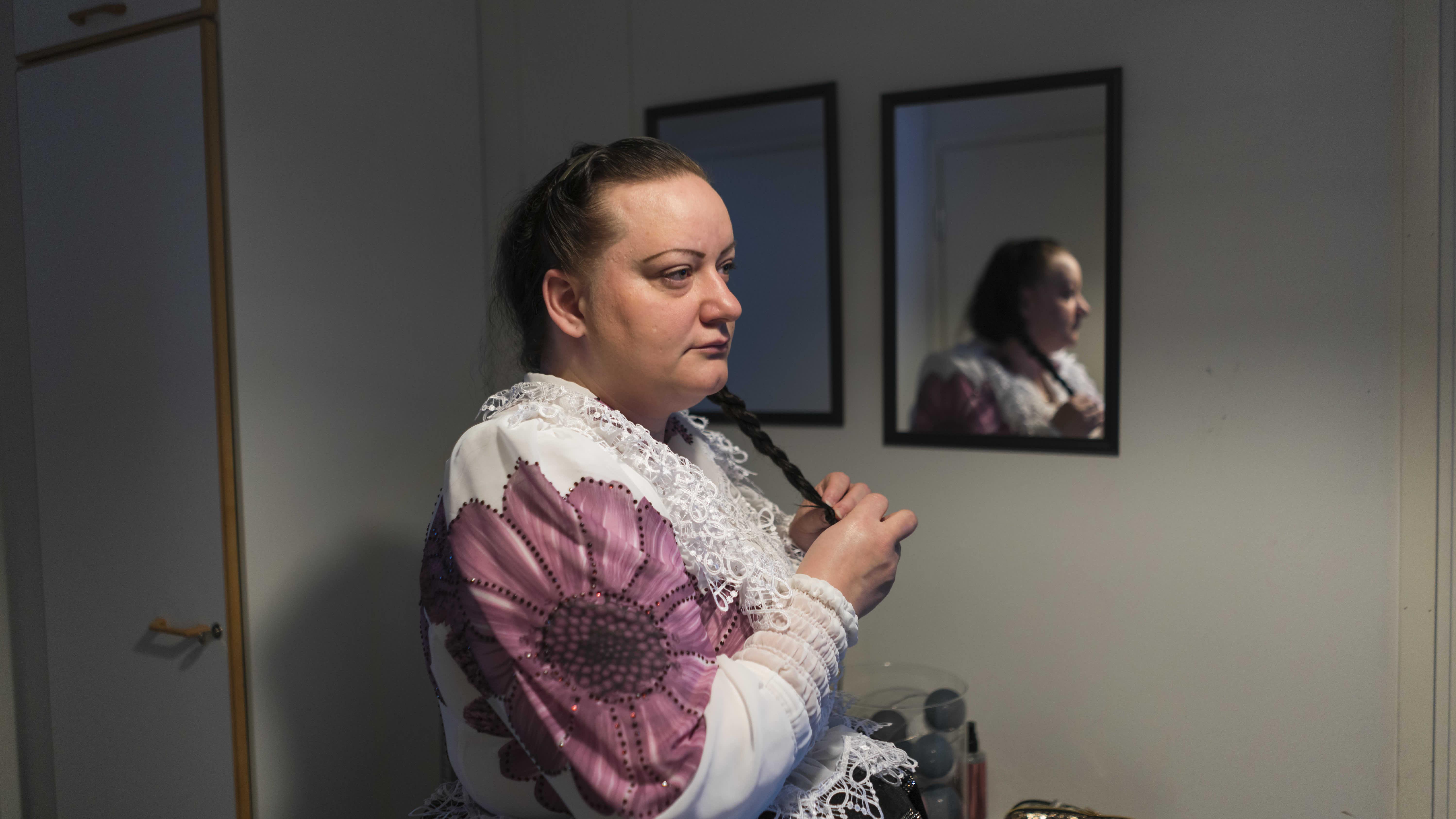 Sonja Lindeman laittaa hiuksiaan. Hänellä on päällään romanien kansallispuku.