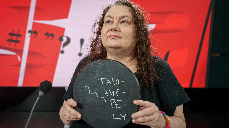 Ohjaaja Susanna Kuparinen pitää pyöreää liitutaulua käsissään Viimeinen Sana-ohjelman lavasteissa