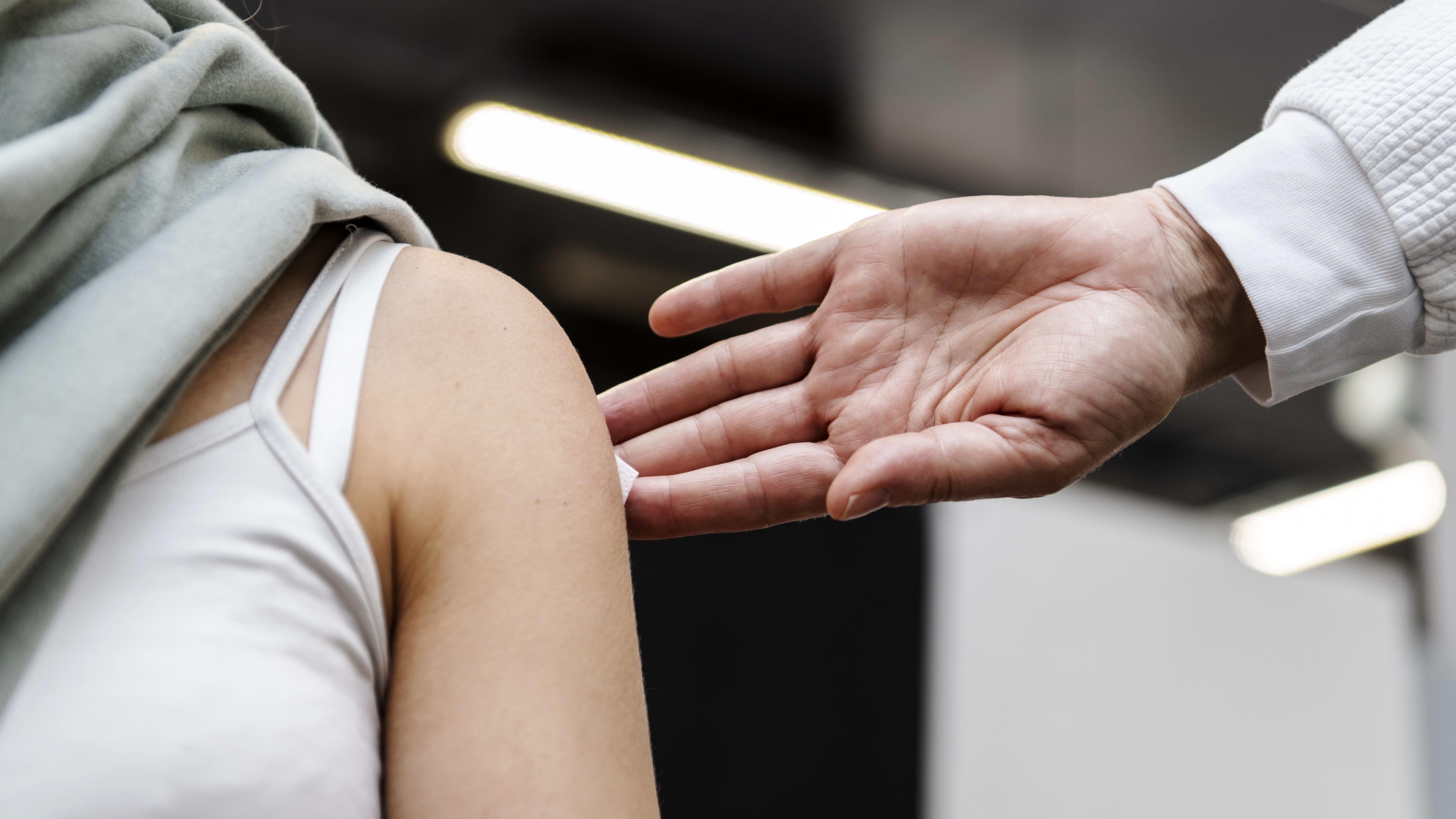 Sairaanhoitaja antoi naiselle koronavirusrokotteen.