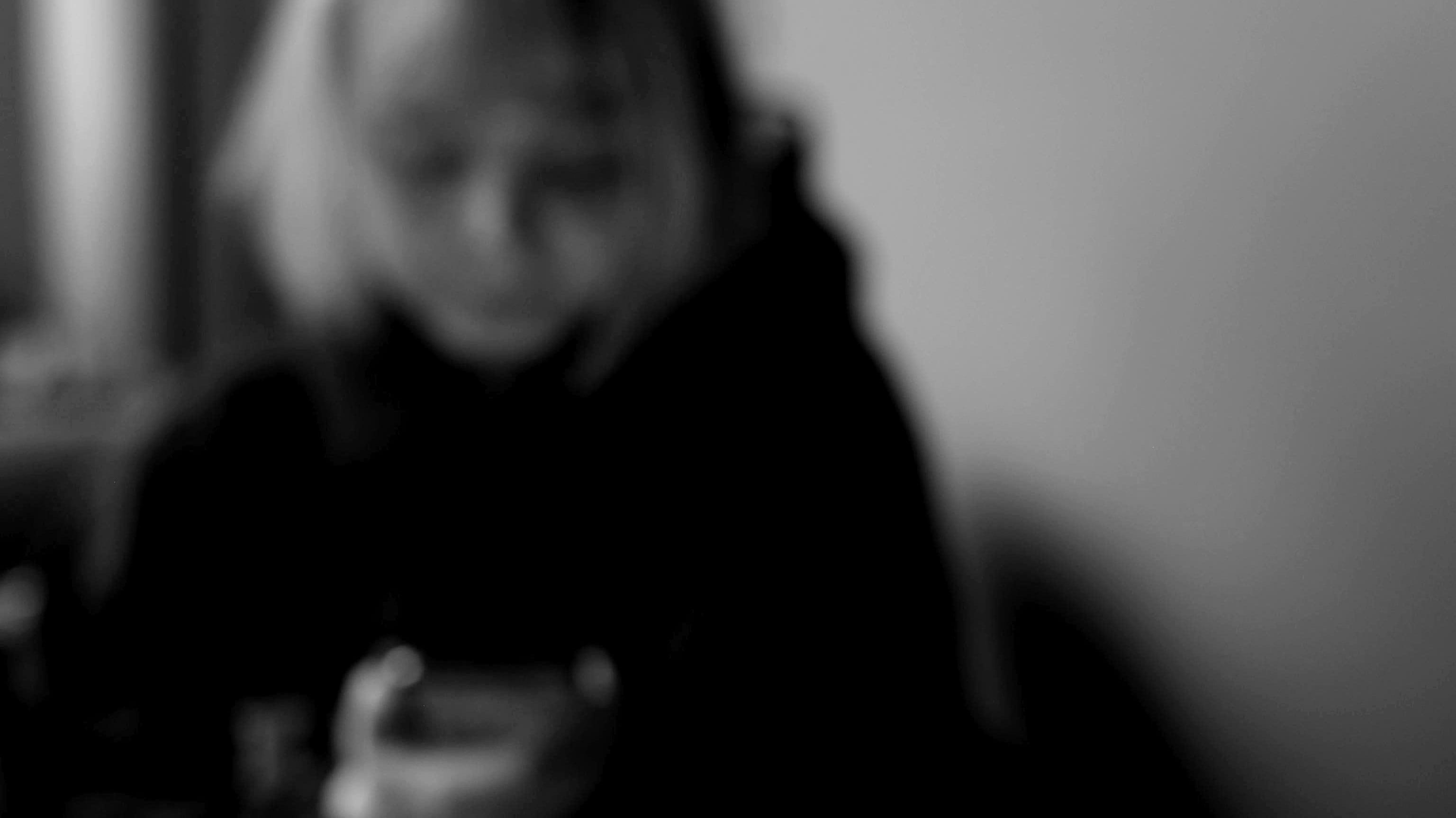 Någon anonym tittar ner på sin telefon. Bilder är svartvit och blurrad.