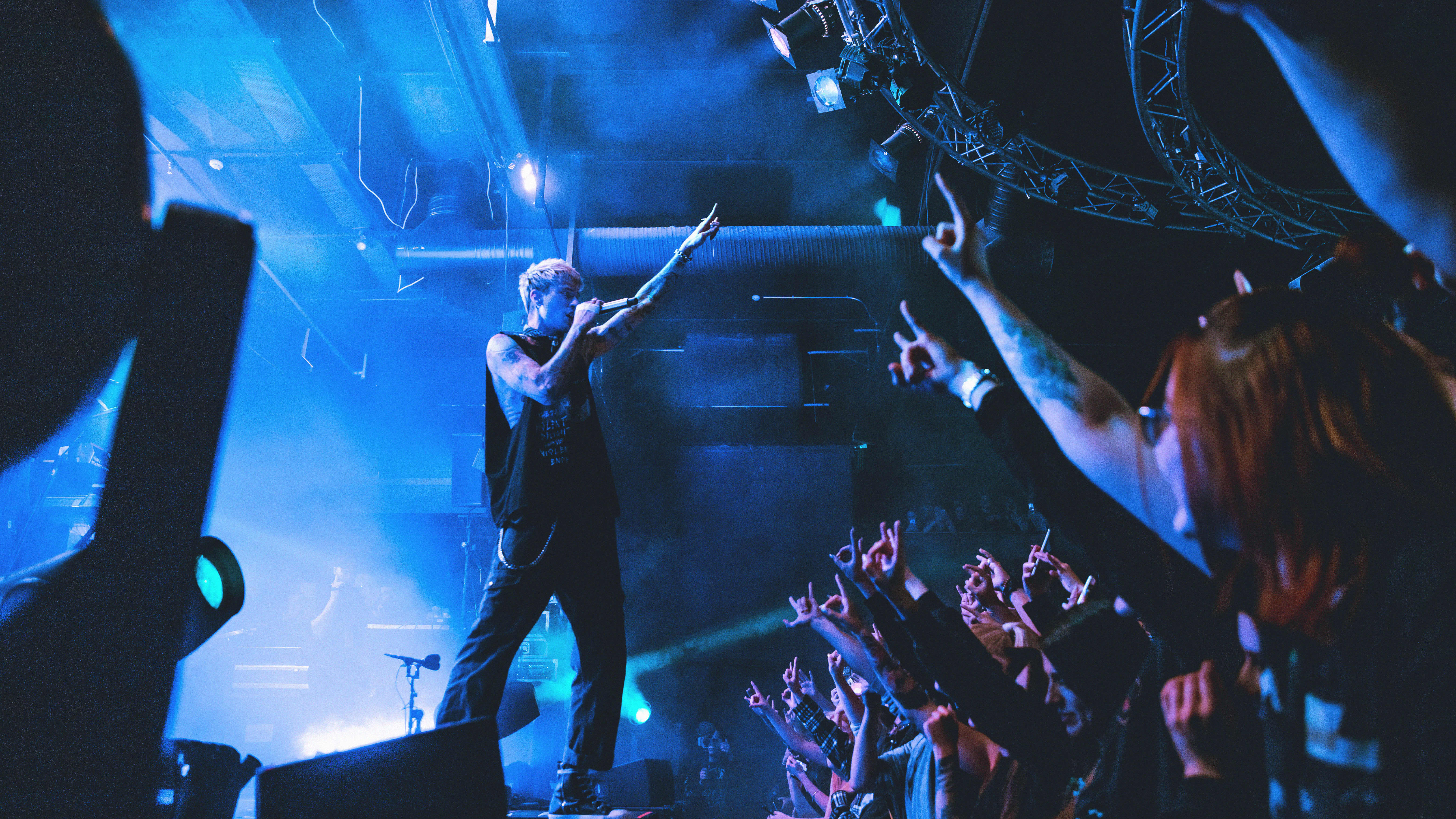Räppäri Machine Gun Kelly seisoo lavalla sormet ojossa pirunsarviasennossa, yleisö vastaa samalal eleellä.