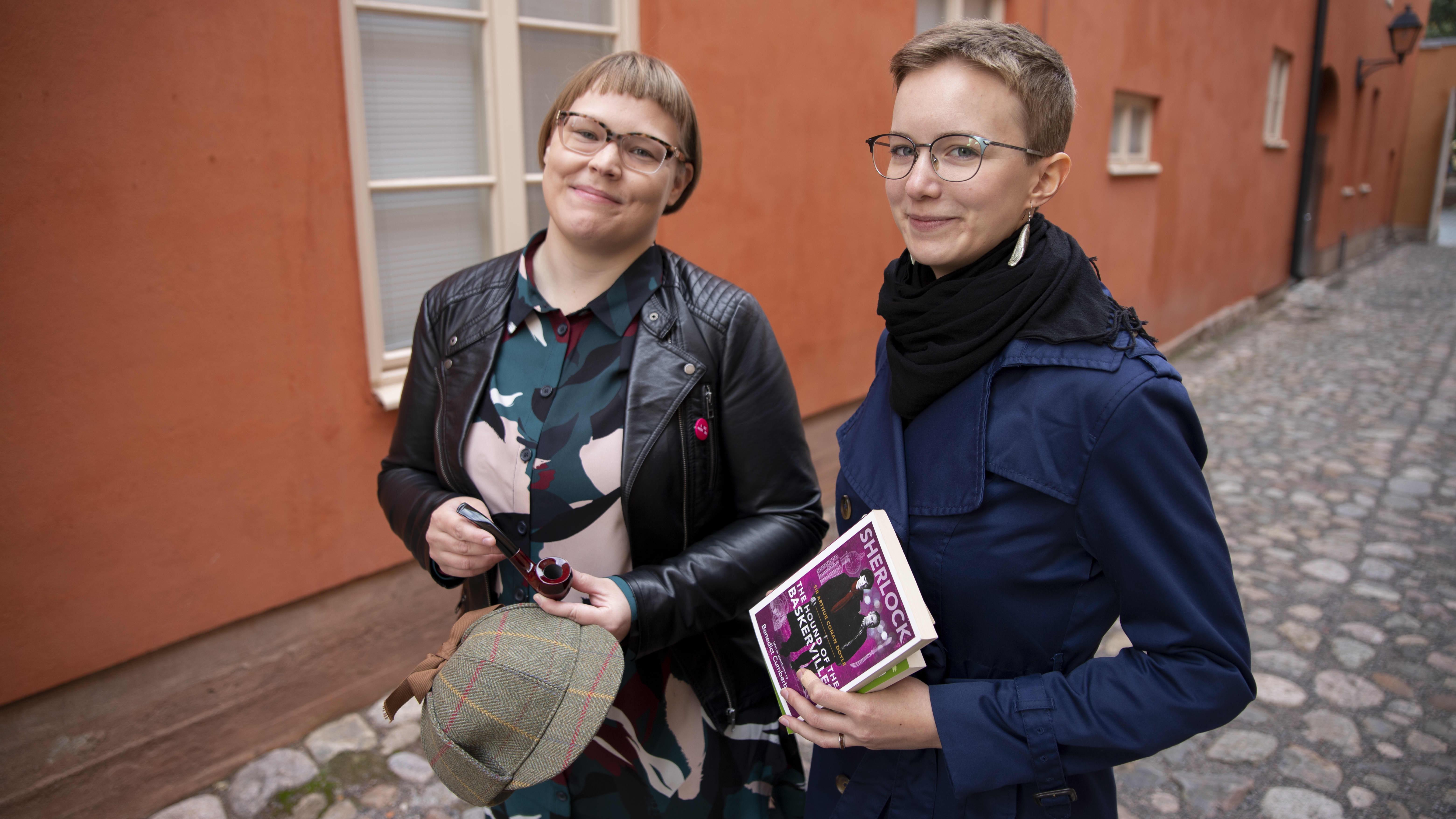 Tutkija Elina Karvo ja Suvi Laine poseeraavat Sherlock Holmesin hatun ja kirjojen kanssa Vanhan Suurtorin maisemassa.