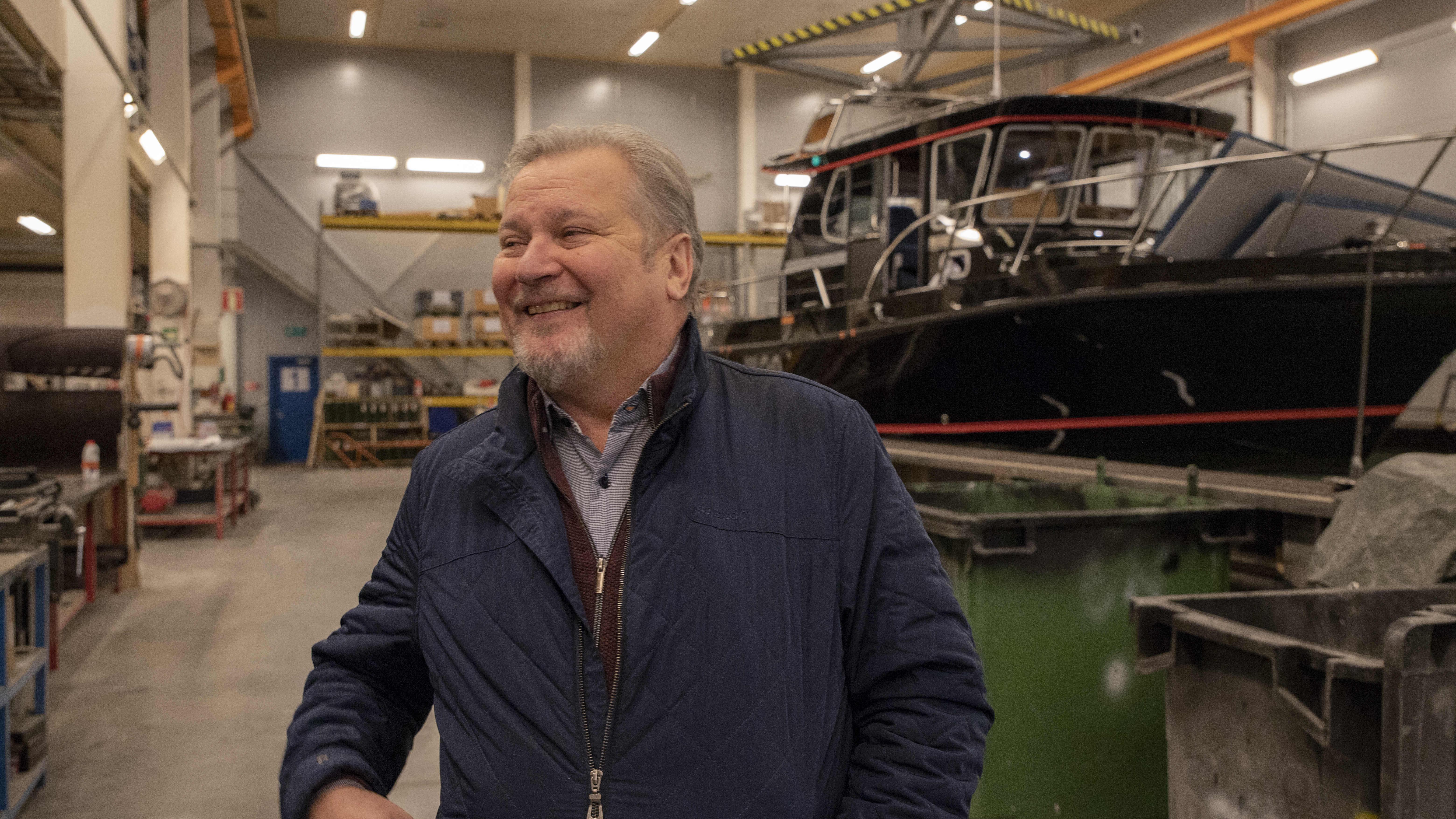 Olli Lindkvist hymyilee veneen rakennus hallissa