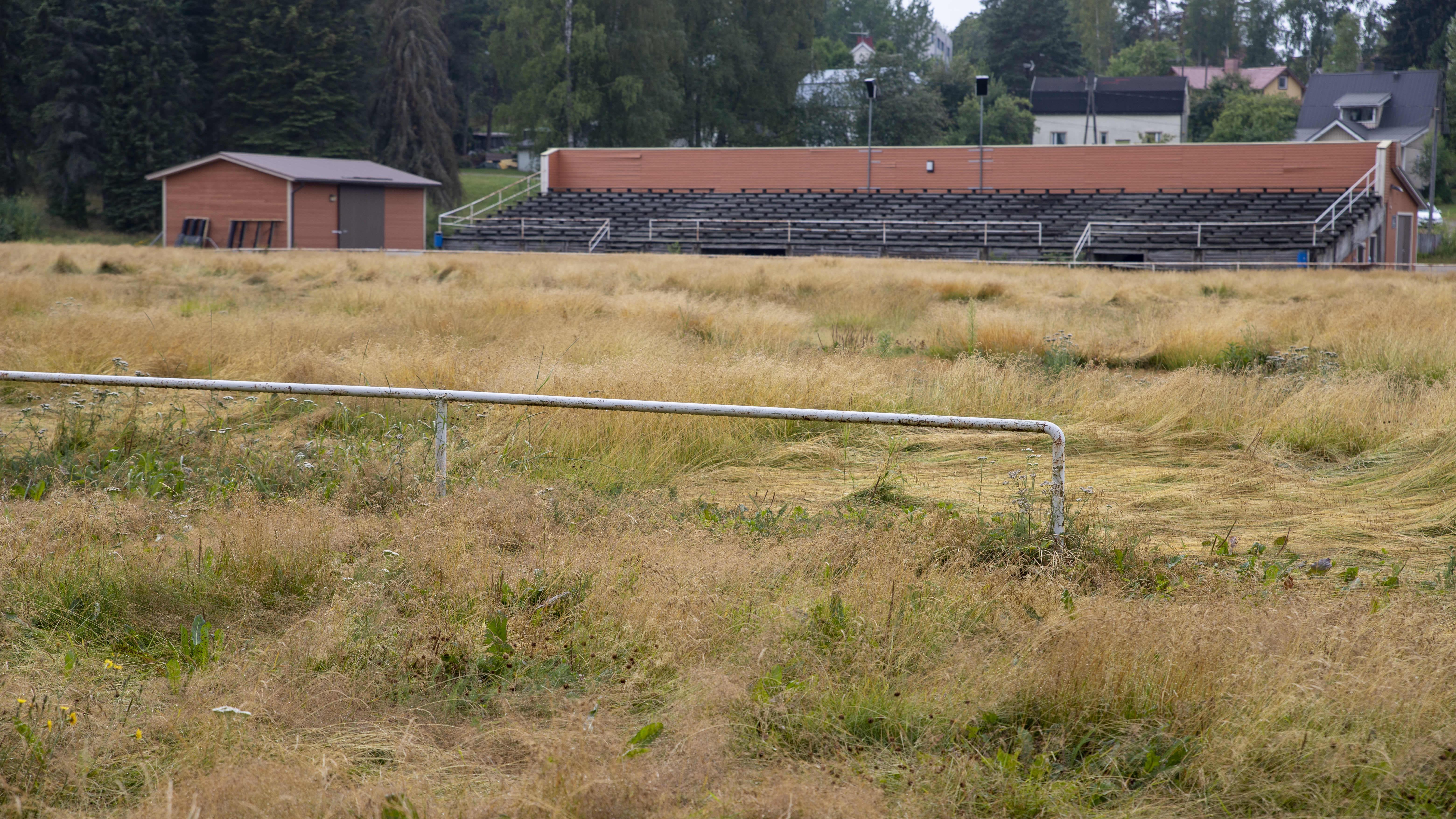 Voikkaan pallokentällä kasvaa heinää, taustalla näkyy huoltorakennus