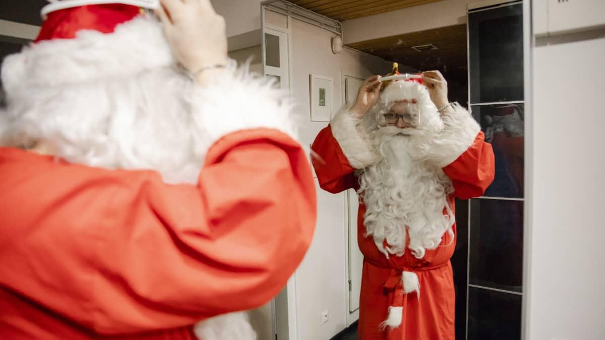 joulupukki laittaa visiiriä päähän