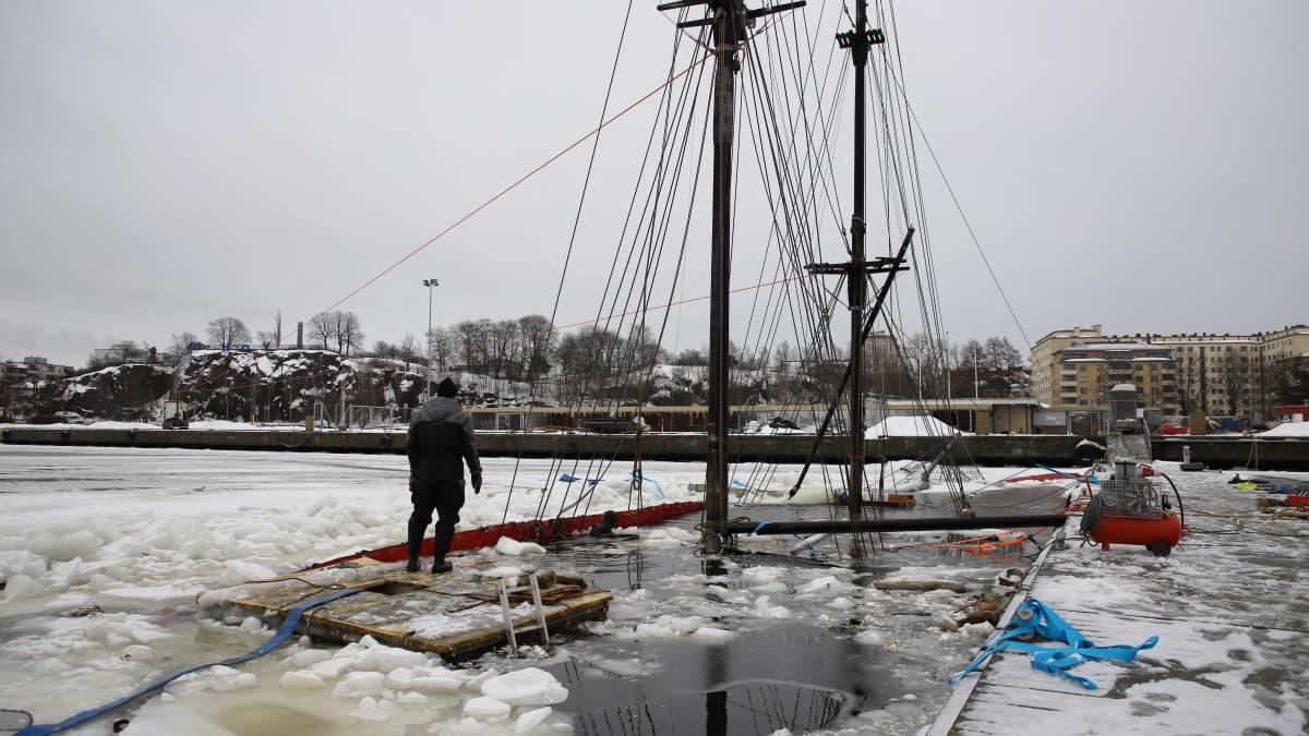 Mies seisoo veden peitossa olevalla purjealuksella