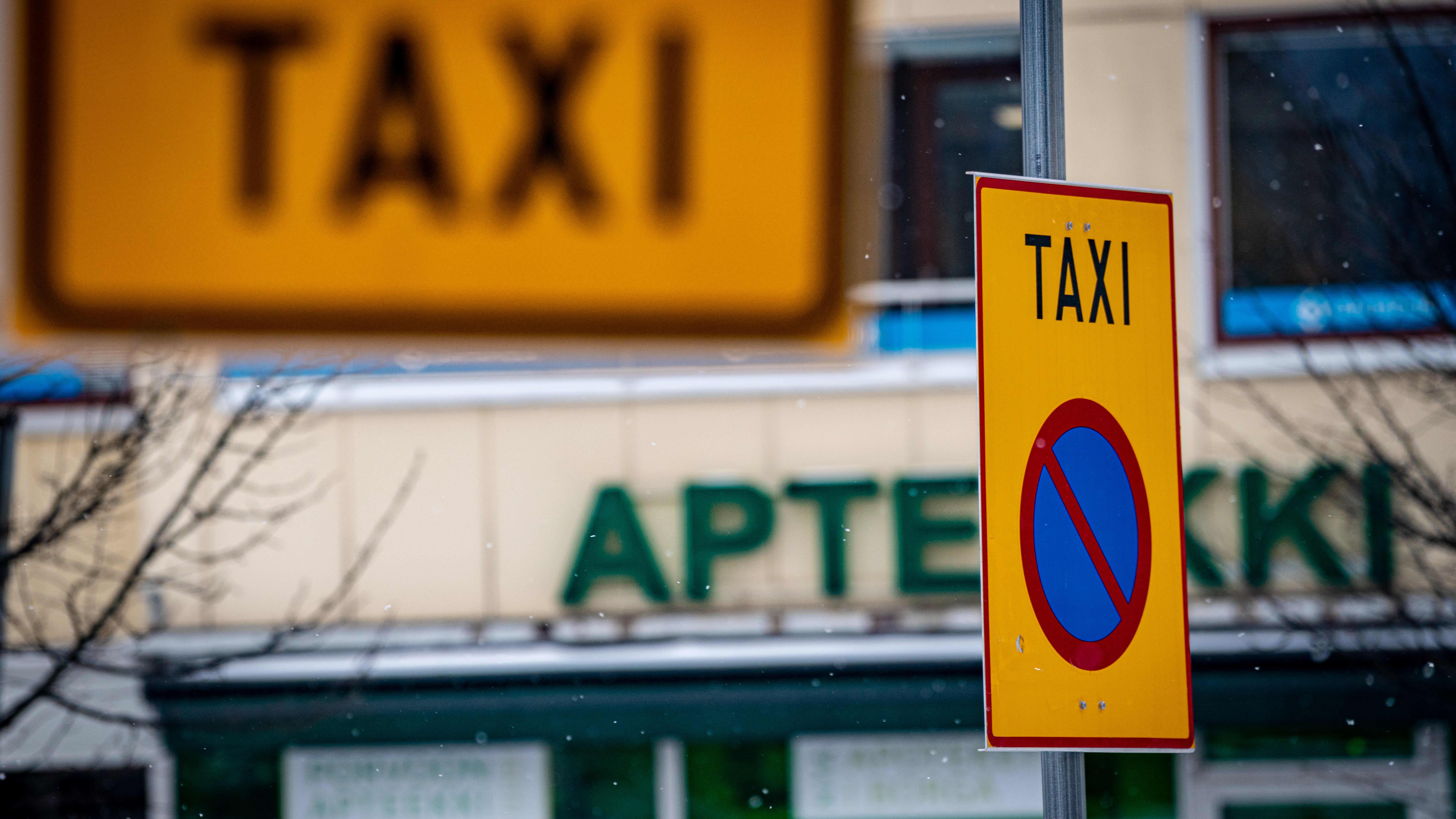Taxi-kylttejä talvisessa kaupunkimaisemassa.