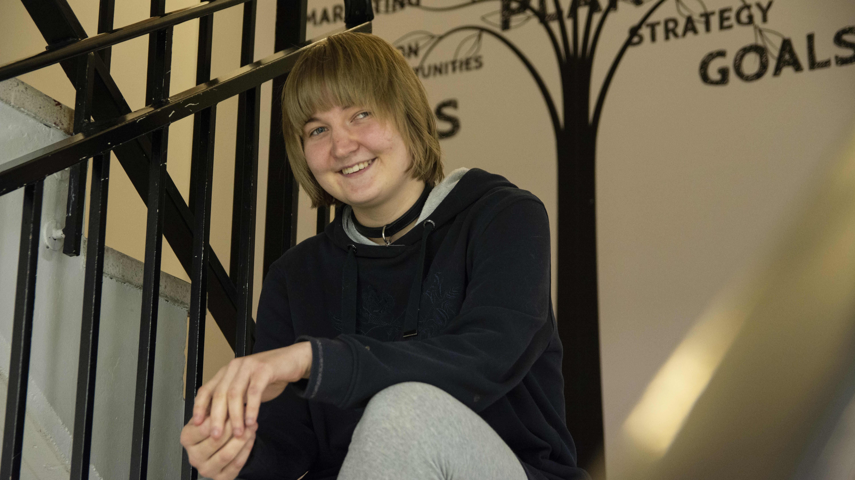 Kaisla Kauppinen istuu kierreportailla ja katsoo hymyillen kameraan.
