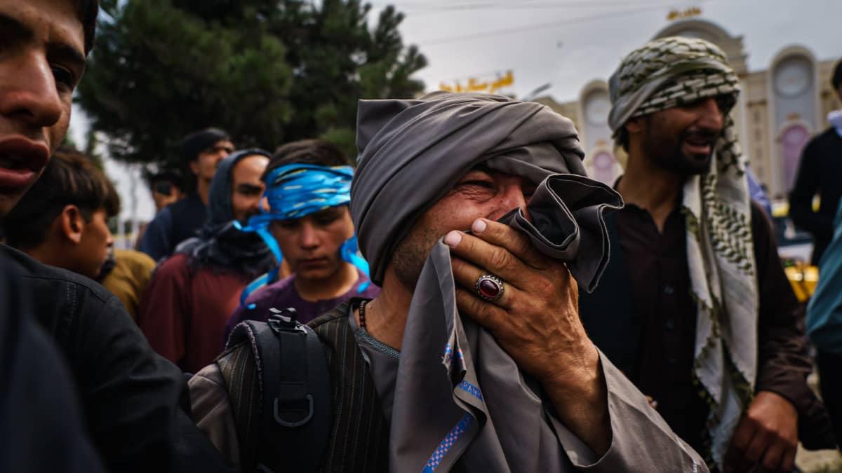 Mies suree kaaoksessa loukkaantuneita ihmisiä Kabulin kansainvälisen lentokentän ulkopuolella tiistaina 17. elokuuta.