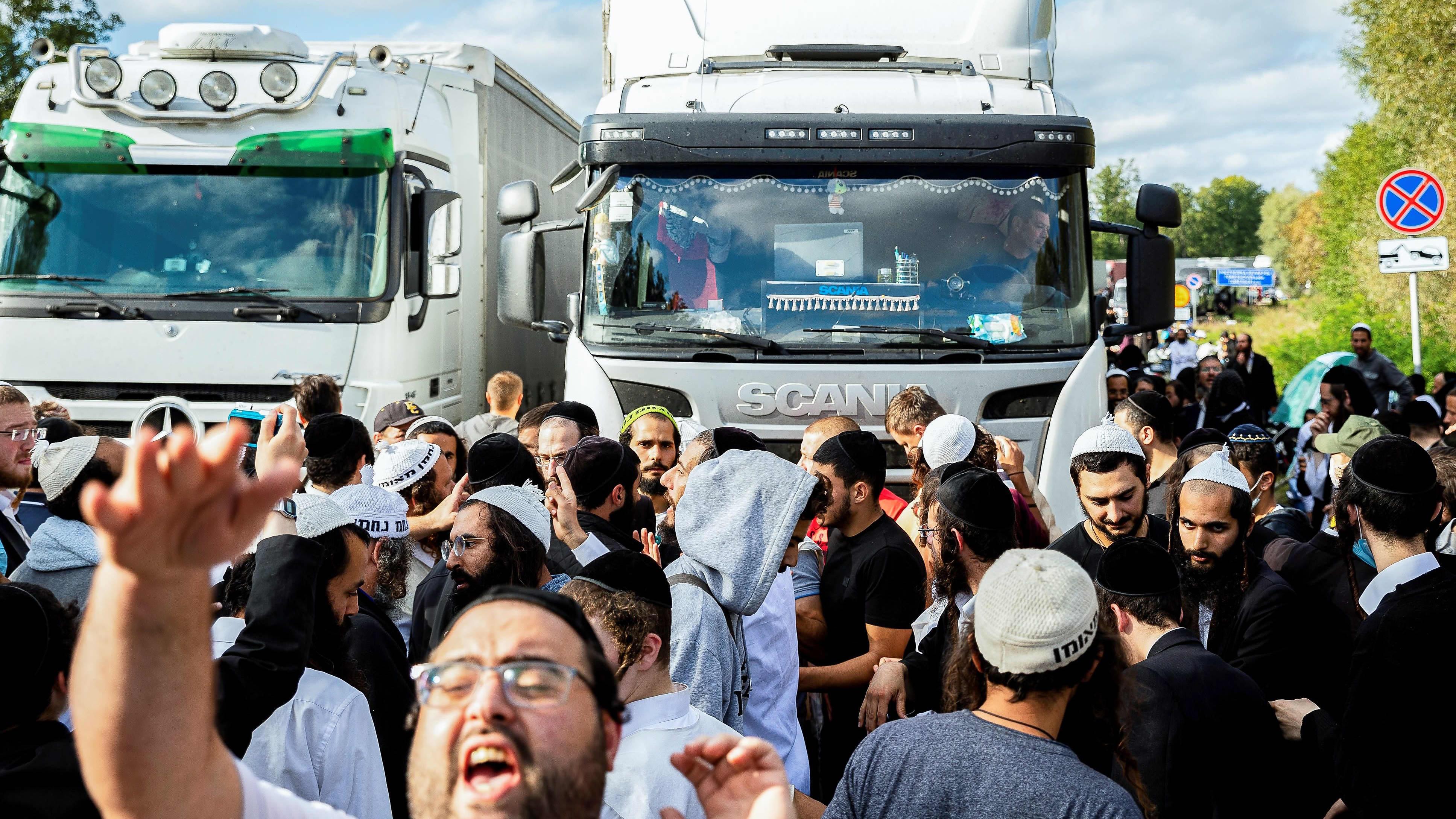 Suuri joukko hasidijuutalaisia on tiellä raja-alueella. Taustalla näkyy kuorma-autoja.