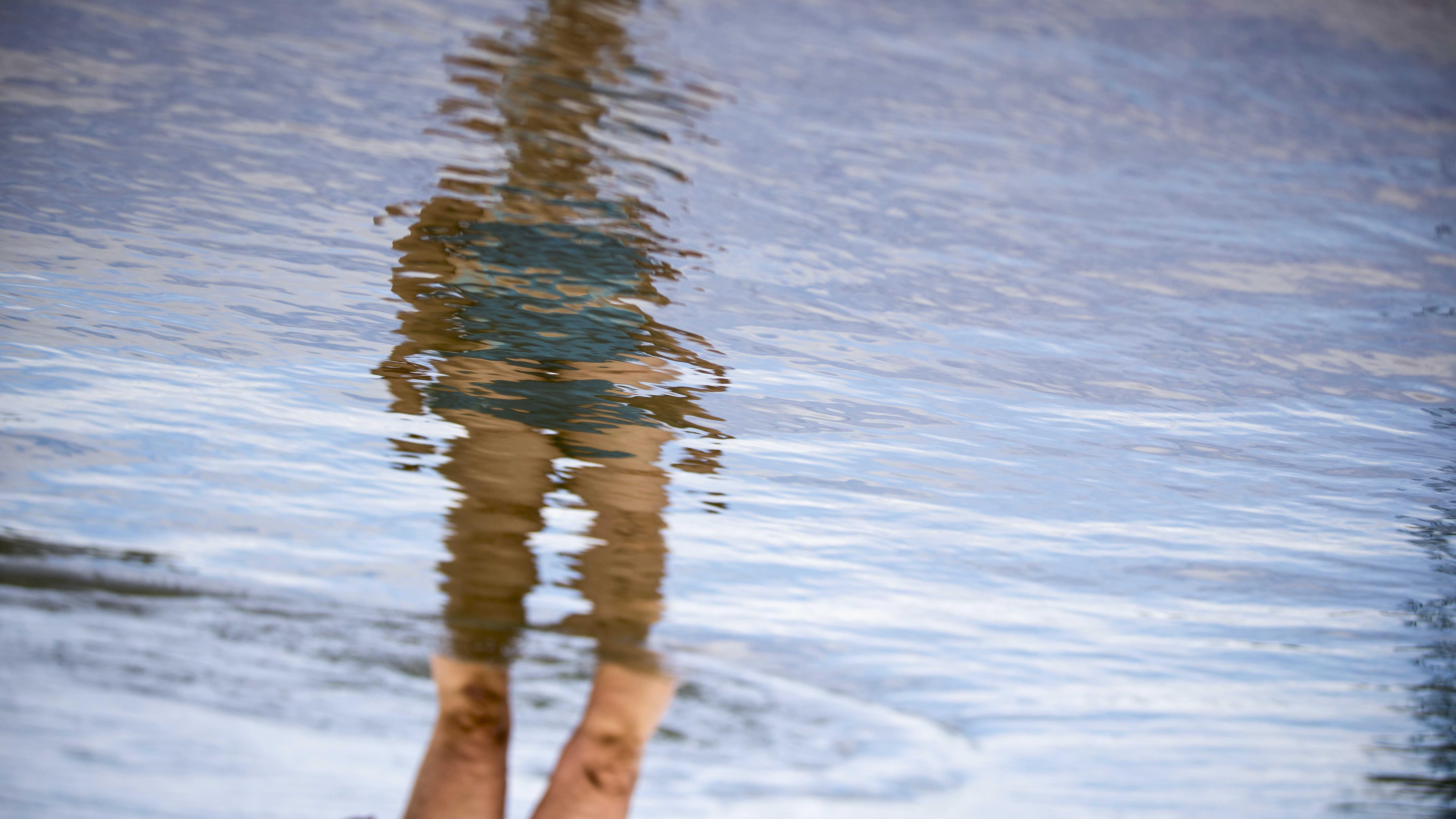 Kuvituskuva uimarin heijastus vedessä, saa kääntää oikeinpäin