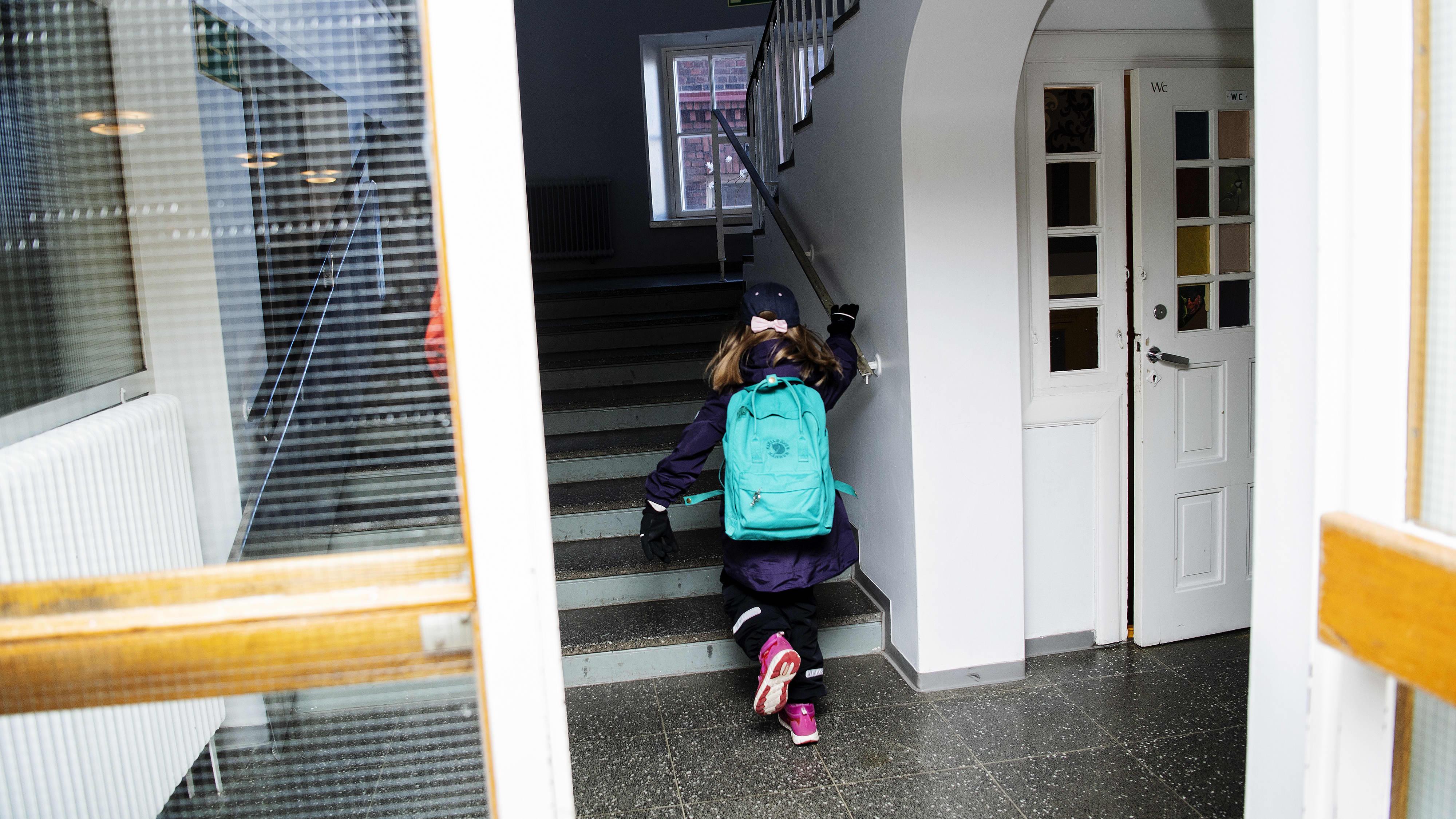 Kuvassa tyttö juoksee ylös portaita pitkin.