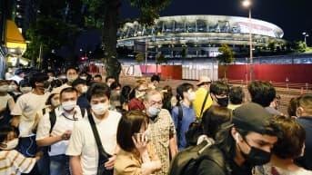 Ihmisiä Tokion Olympia areenan luona.