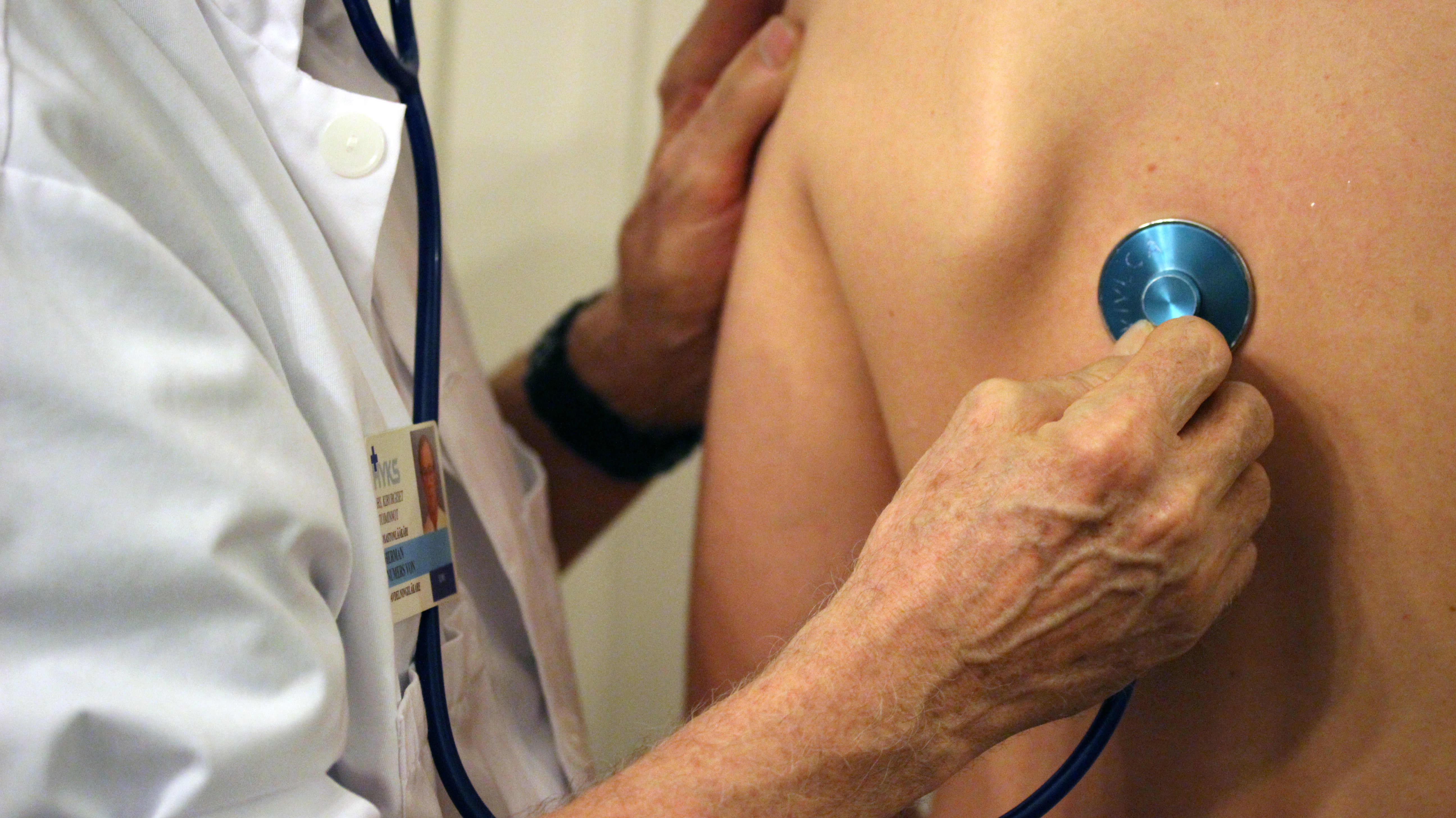 Lääkäri tutkii potilasta stetoskoopilla.