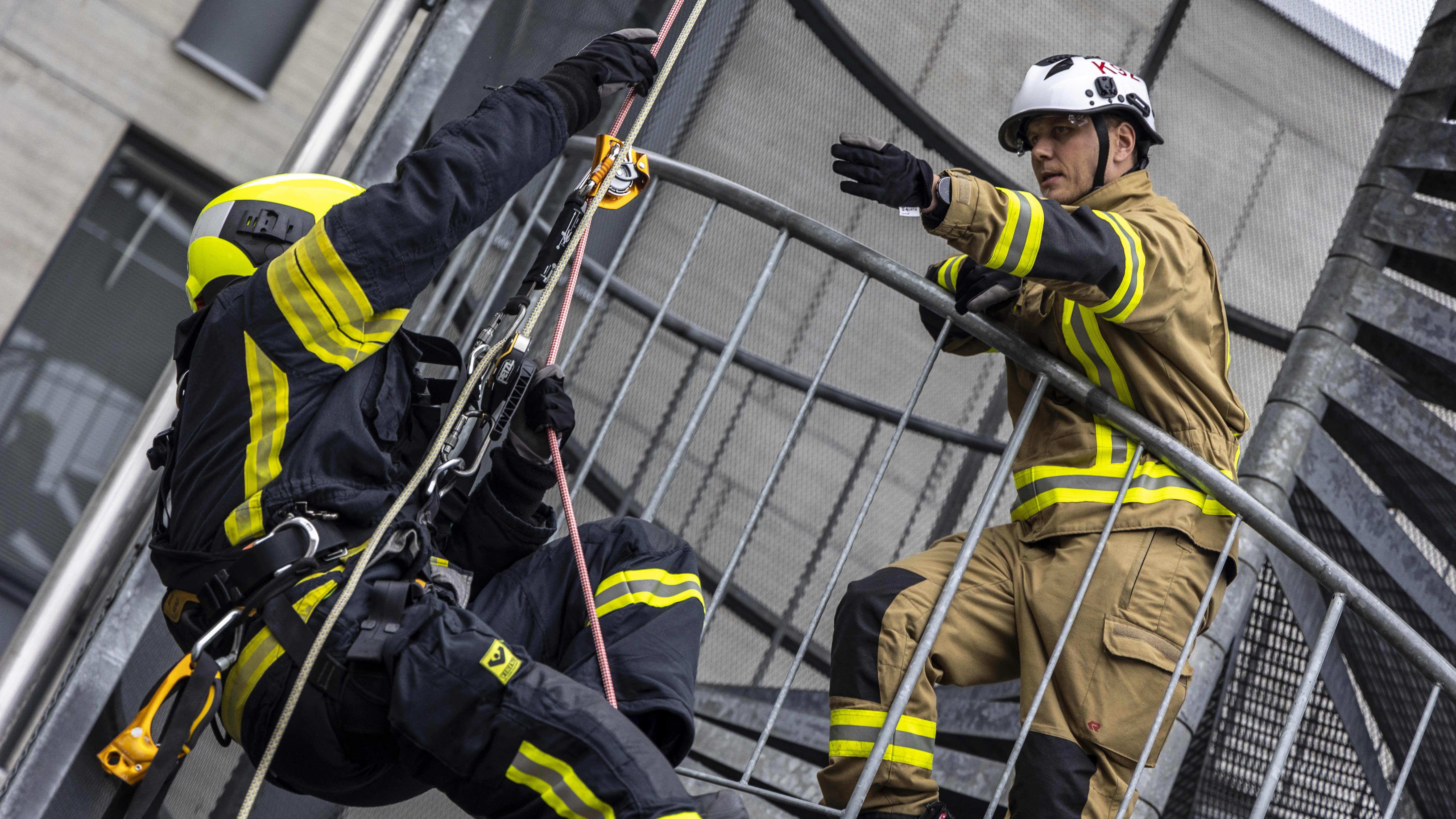 Kouluttaja antaa ohjeita pelastaja opiskelijalle, samalla kun hän laskeutuu korkeasta tornista köyttä käyttäen.
