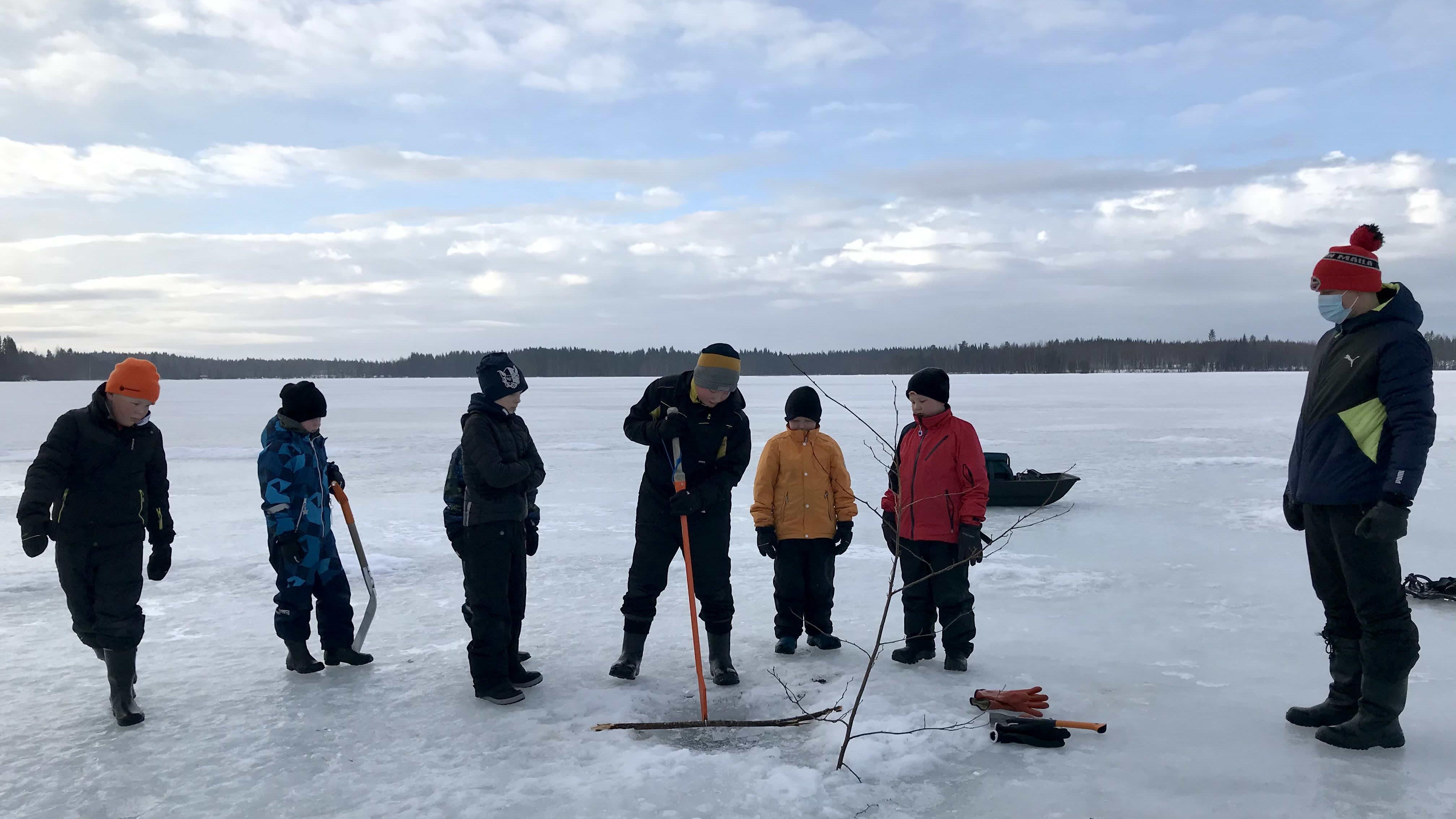 Kangasniemen Äkryn koululaisia jäällä, avantoa kairataan.