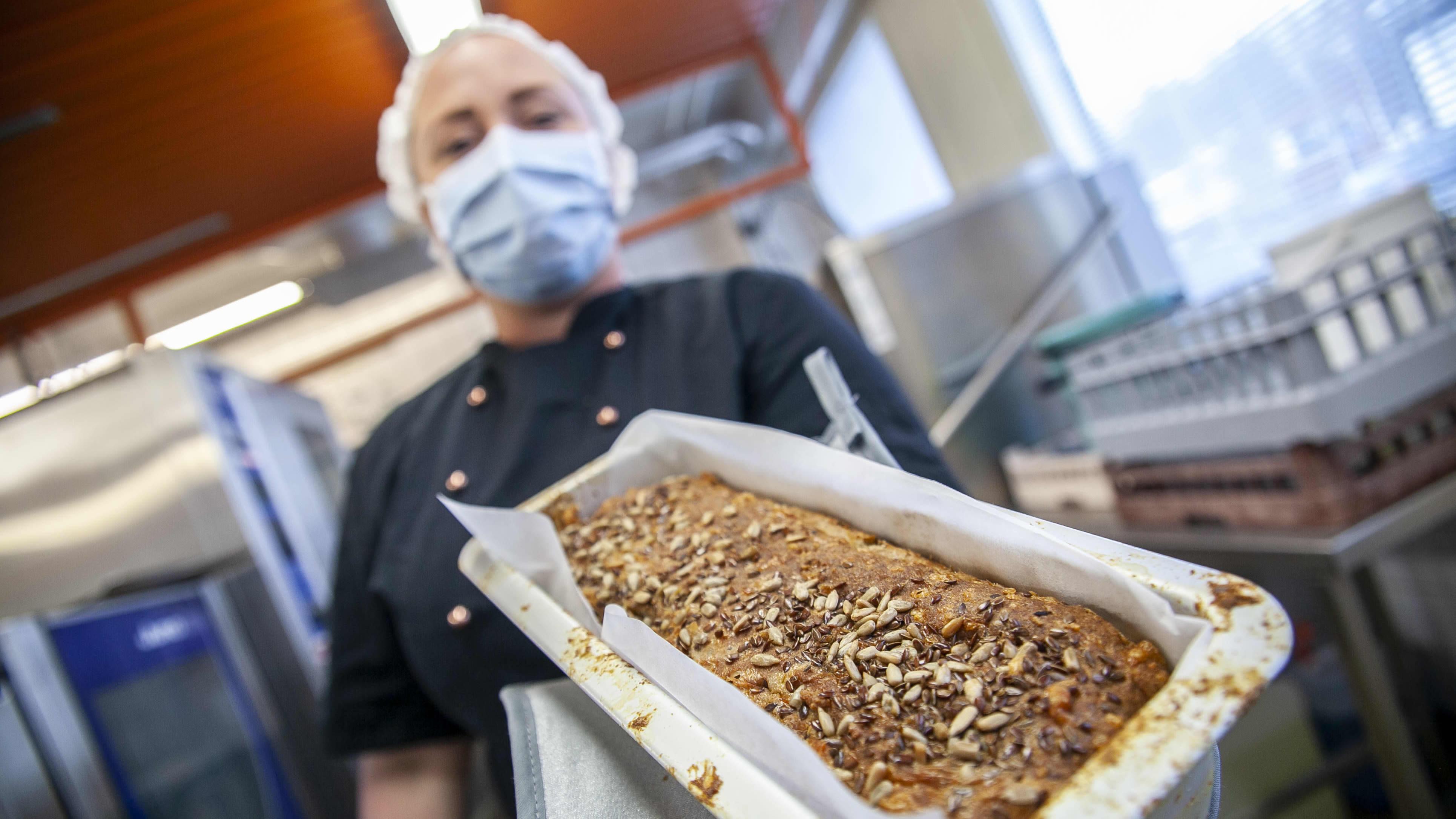 Niina-Marika Lahnavik-Hoffren pitelee mm. hänen kehittelemäänsä viljatonta leipää käsissään Kuopion leipomossa.