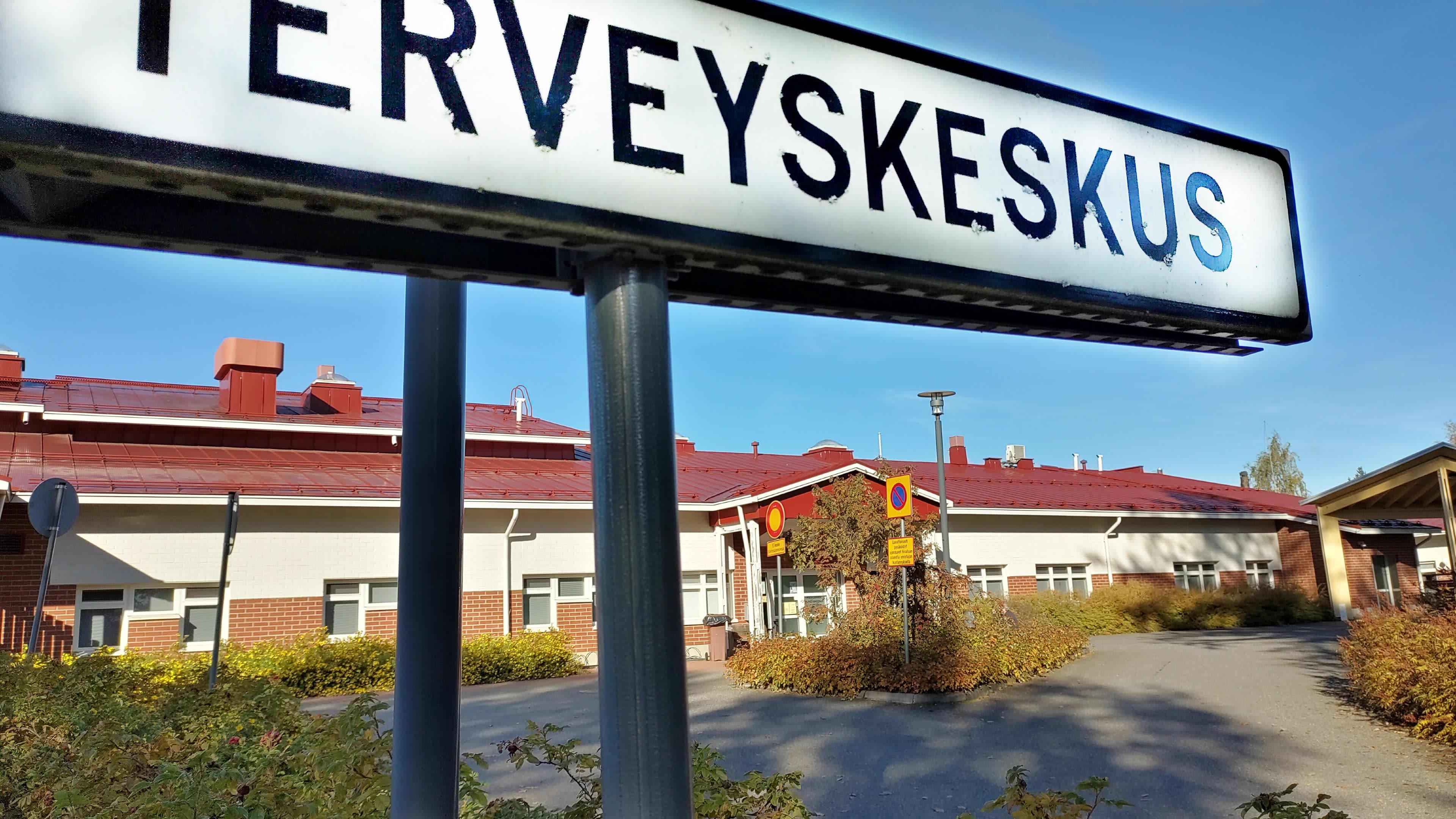 Polvijärven terveyskeskuksen pihaa. Etualalla kyltti.
