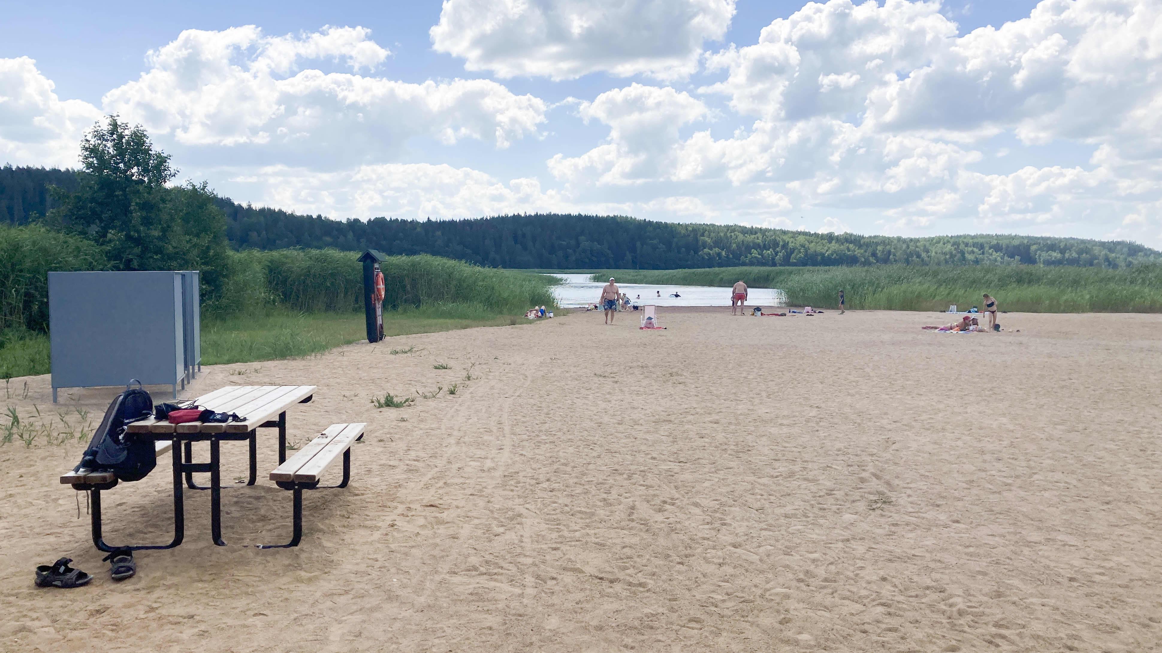 Yleiskuva Raadelman uimarannalta, ihmisiä kaukana veden rajassa.