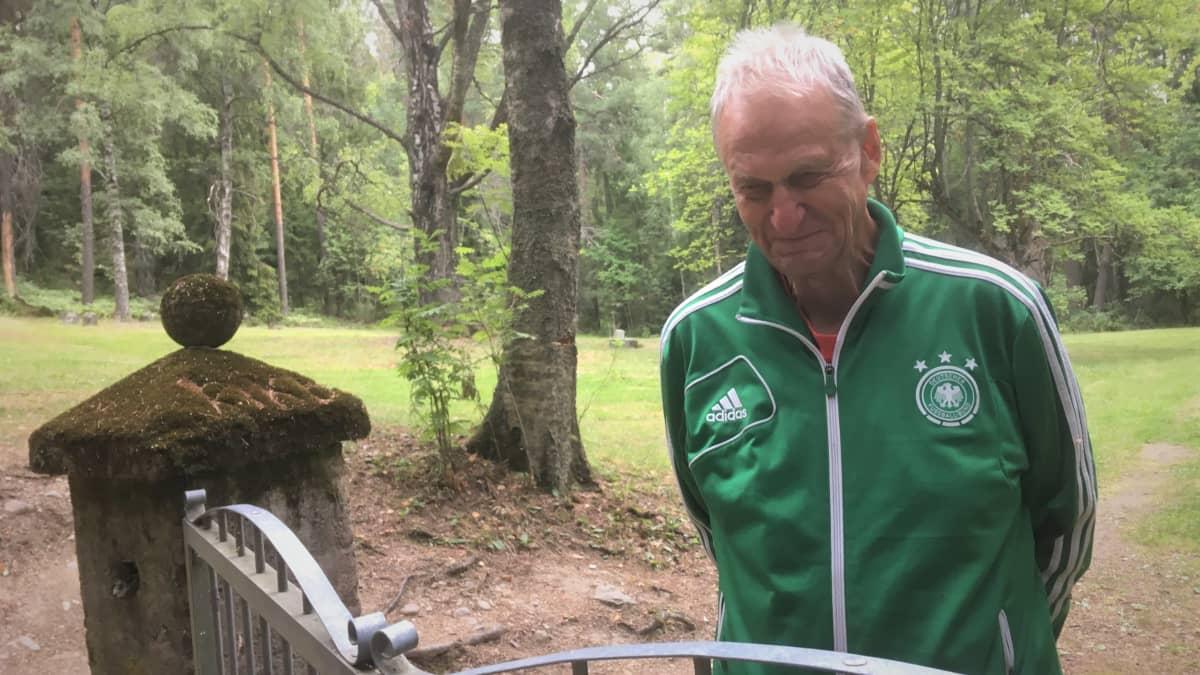 Onni Torikka seisoo Pitkäniemen vanhan hautausmaan portilla