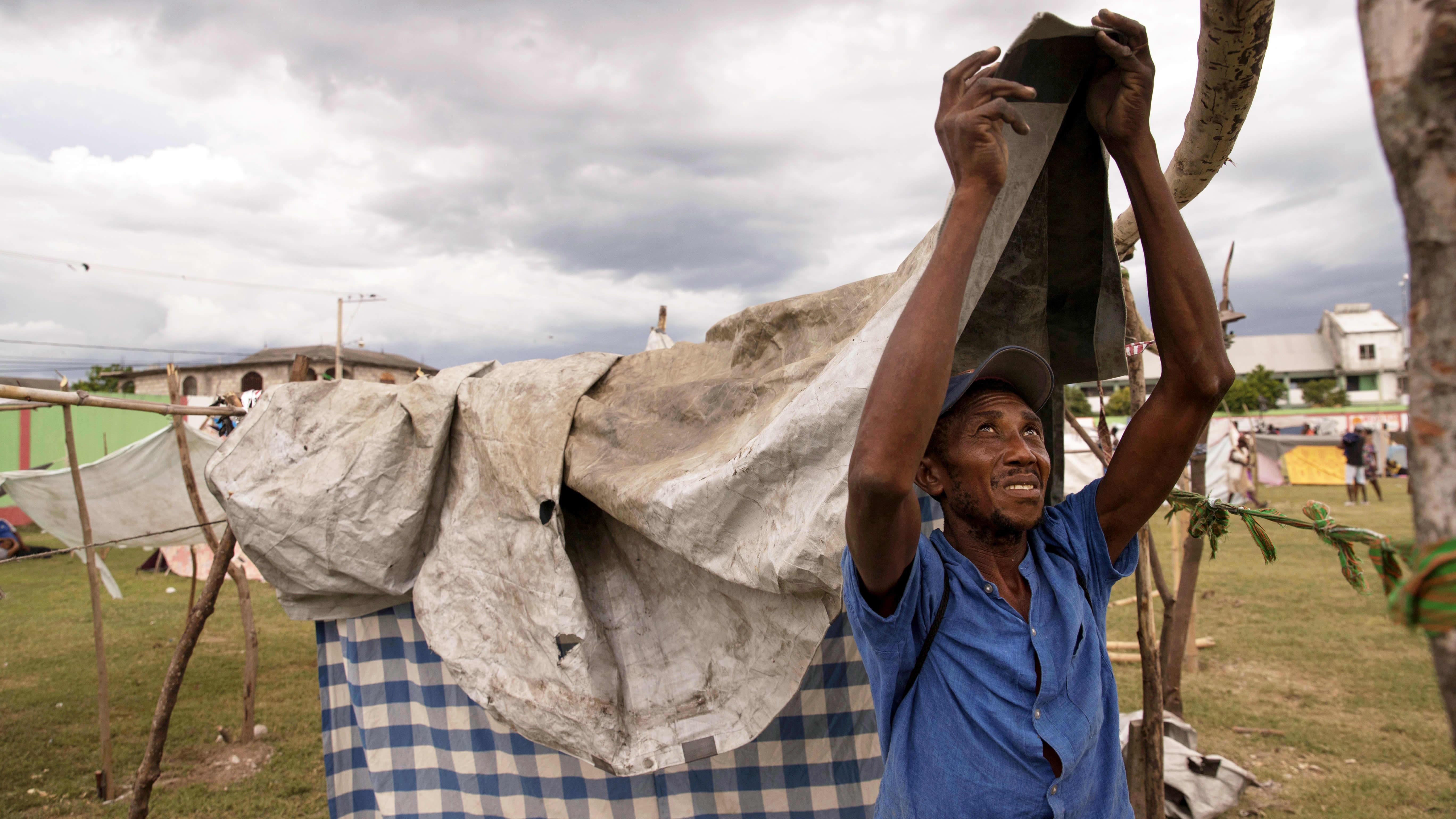 Ihminen rakentaa sateensuojaa väliaikaisen majoituksen leirissä Haitissa, lähestyvältä myrskyltä suojaamaan.