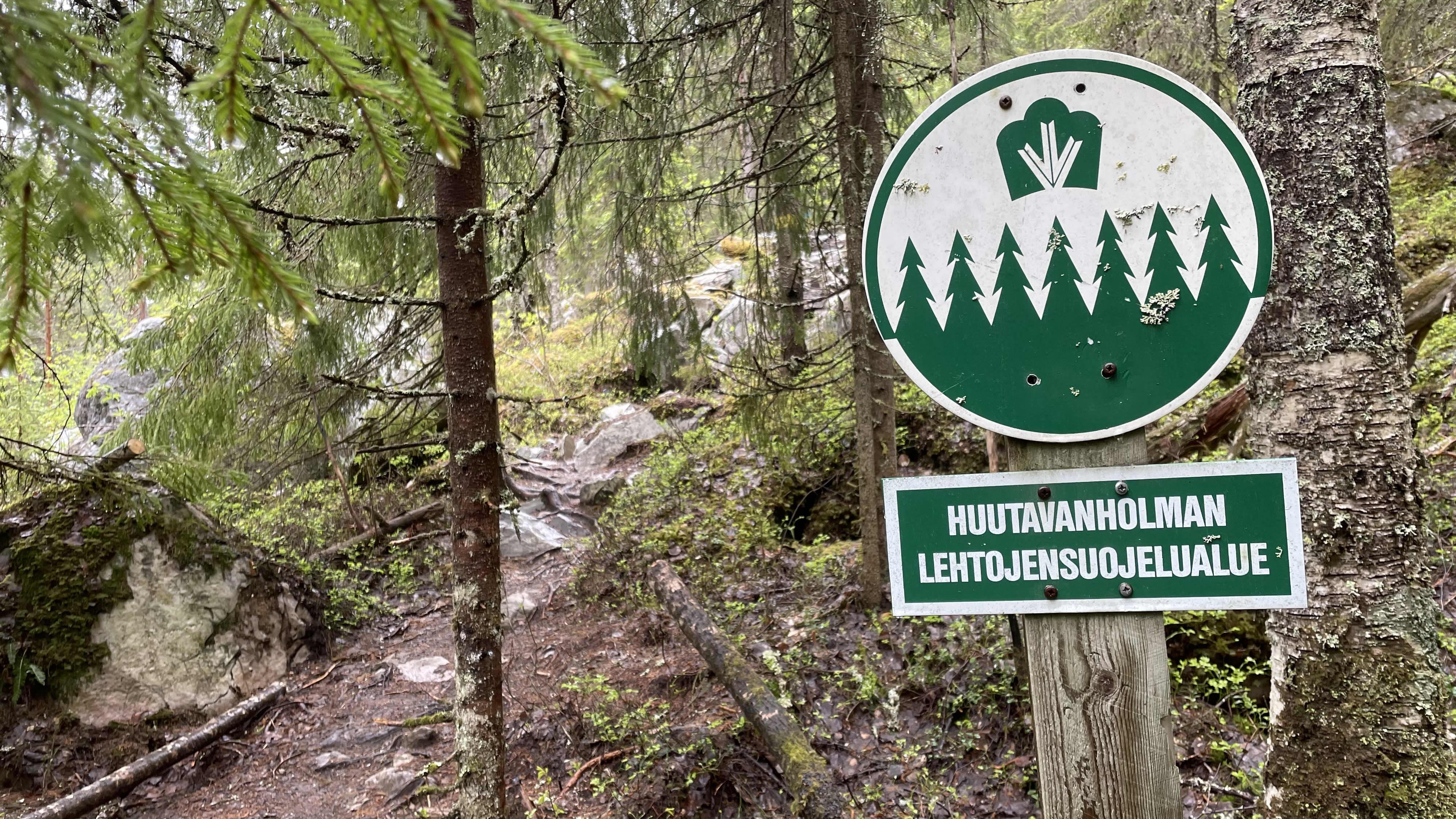 Lehtojensuojelualueesta kertova kyltti metsässä