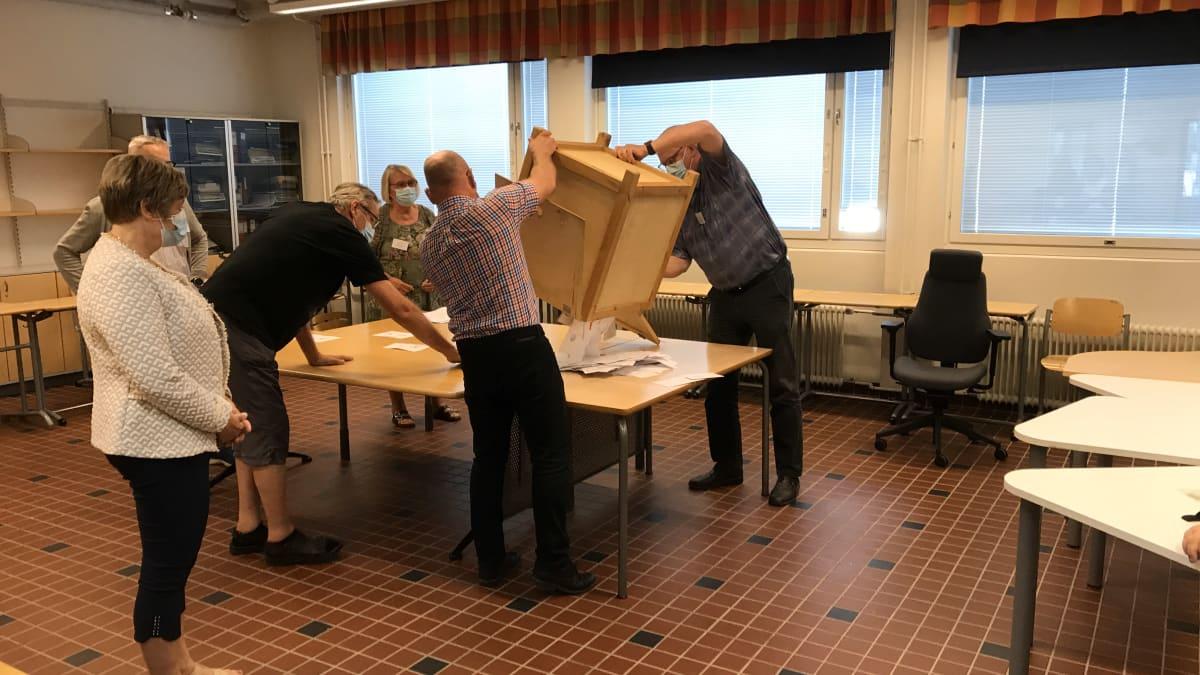 Äänestyslappuja kaadetaan pöydälle.