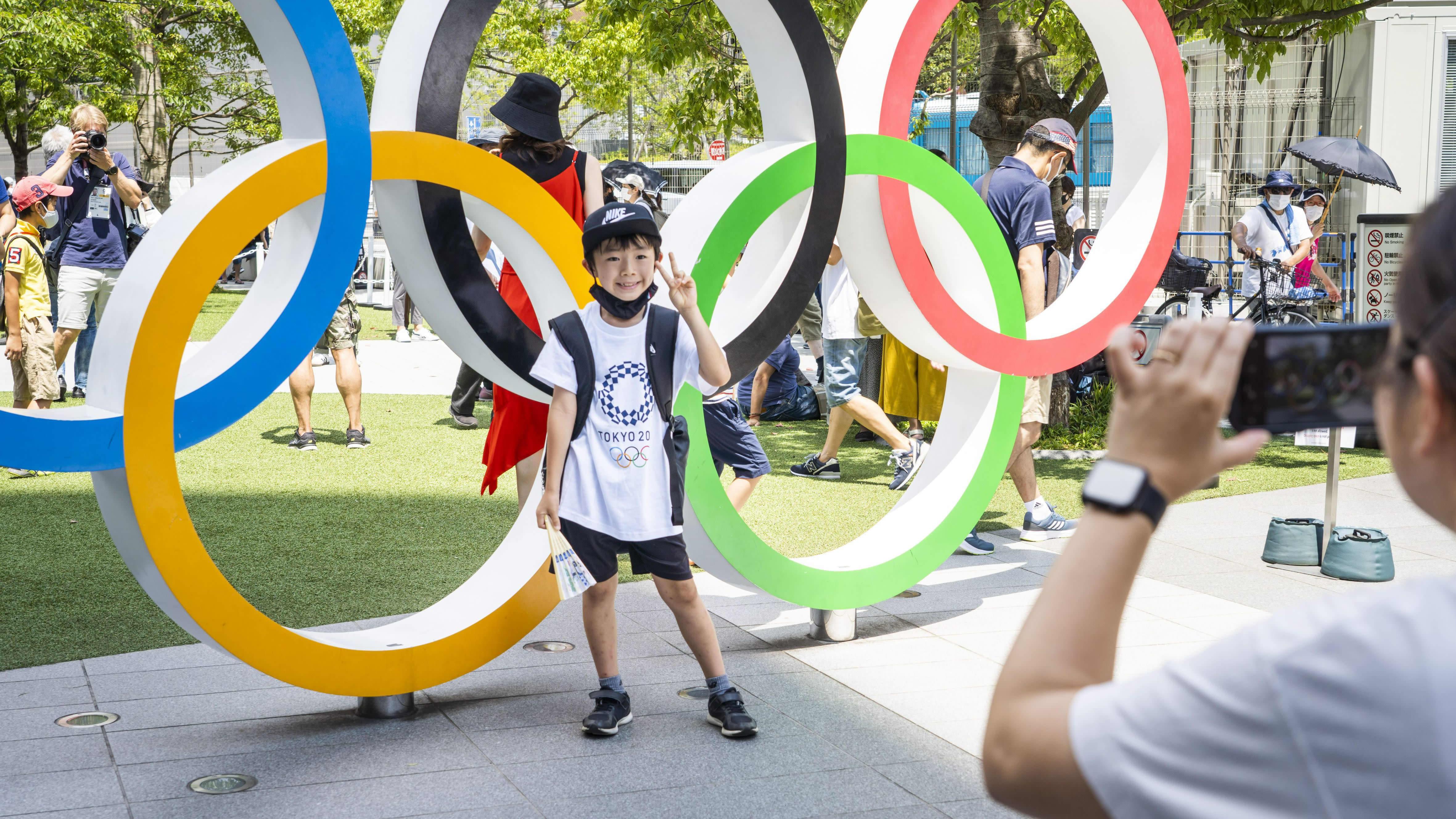 I förgrunden blommor på ett träd, i bakgrunden logon för OS i Tokyo.