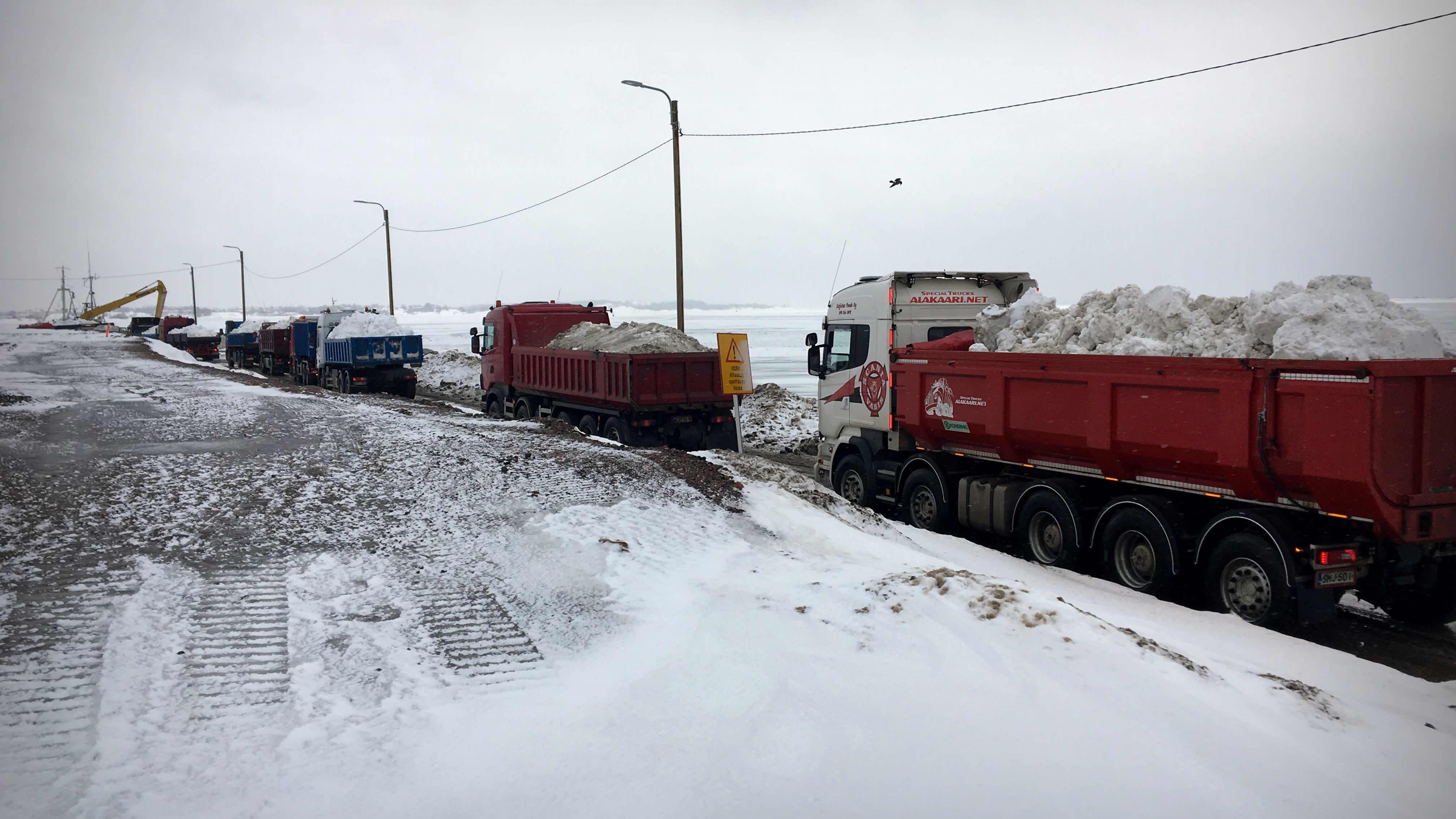 Kuorma-autot vievät lunta kohti Helsingin Hernesaaren kärjessä sijaitsee merityhjennyspaikkaa.