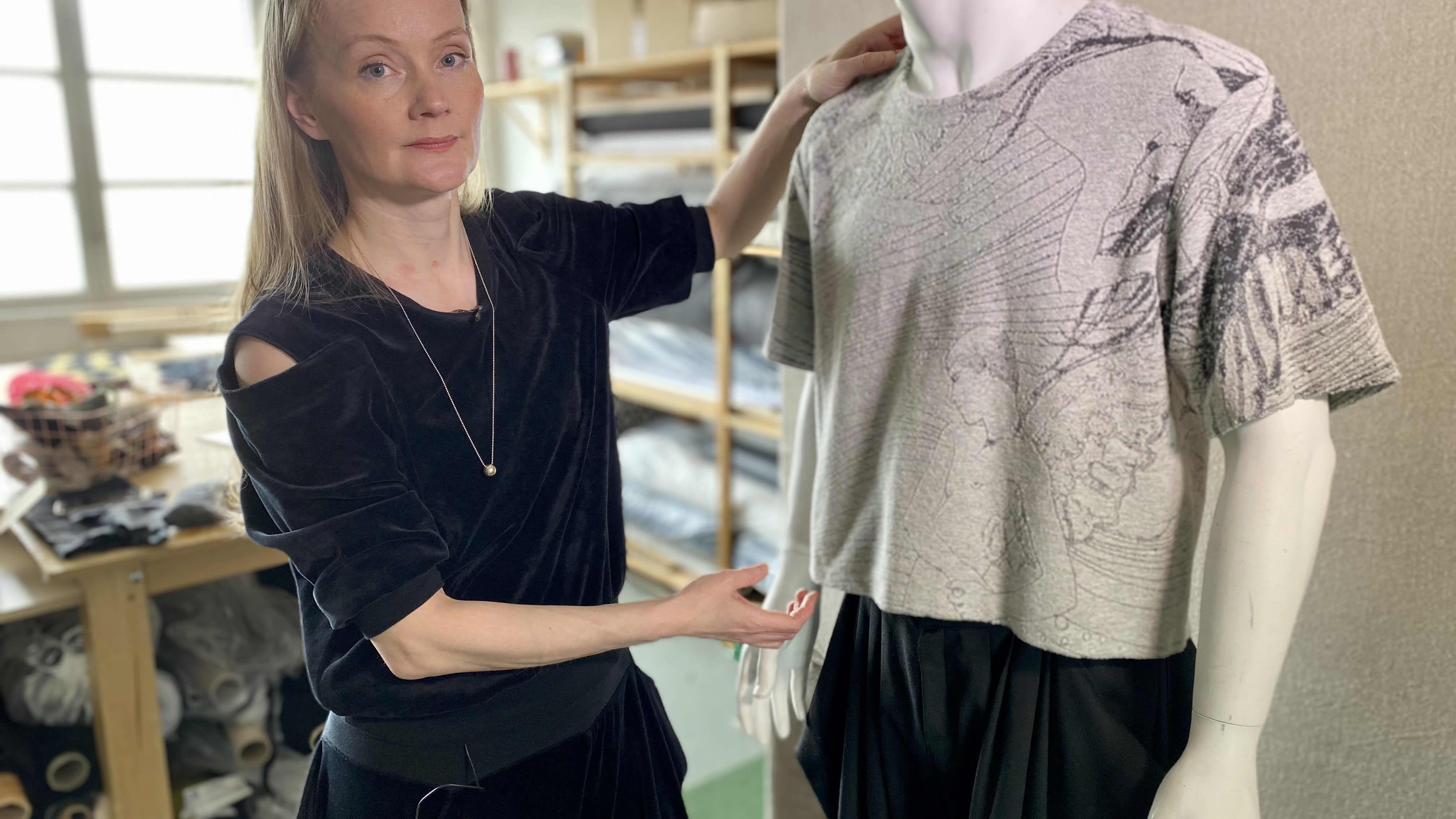 Vaaleahiuksinen nainen sovittaa t-paitaa muotinuken päälle.