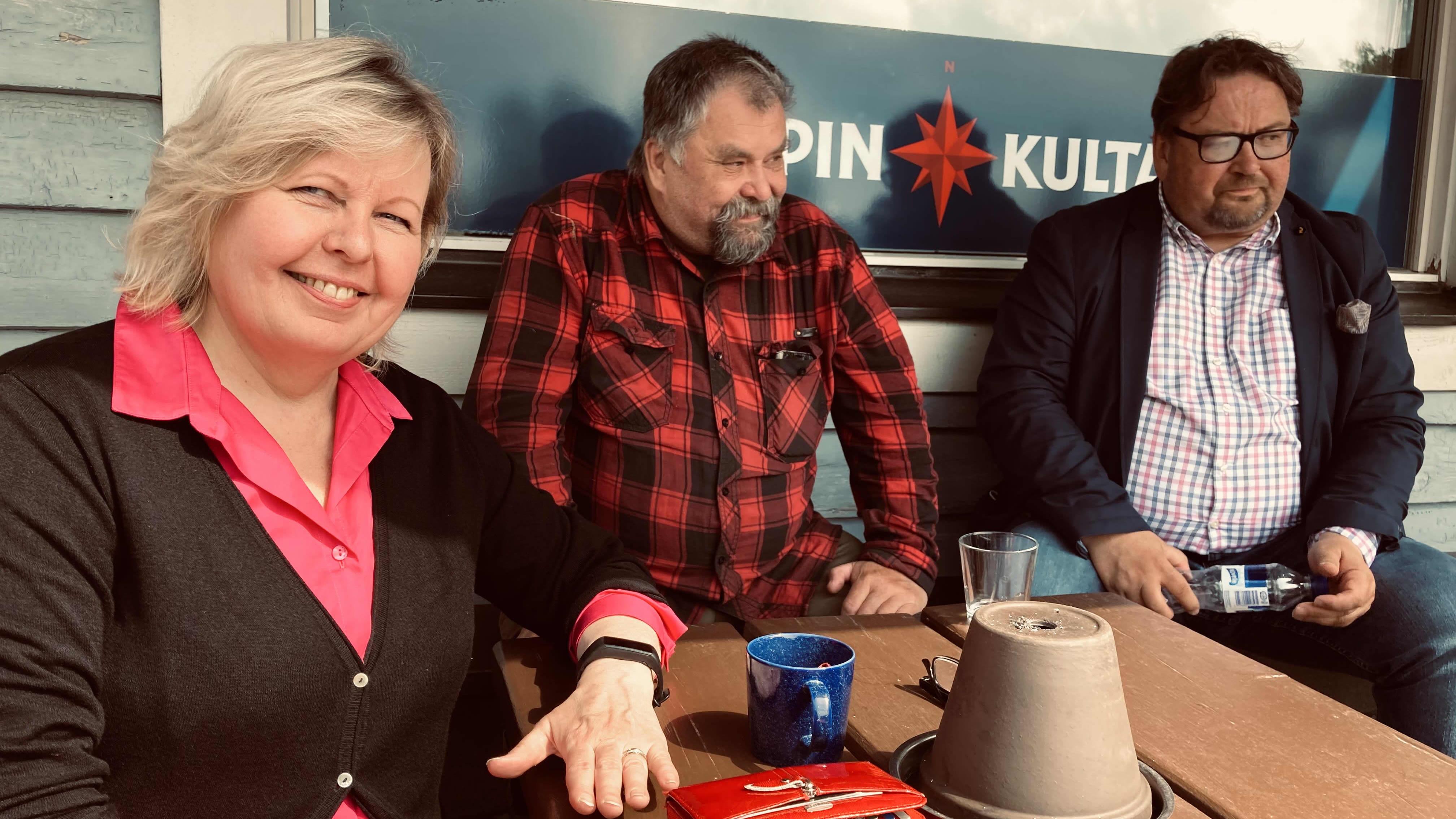 Minna Koskinen, Taavi Riihelä sekä Esa Mikkonen istuvat ravintolan terassilla.