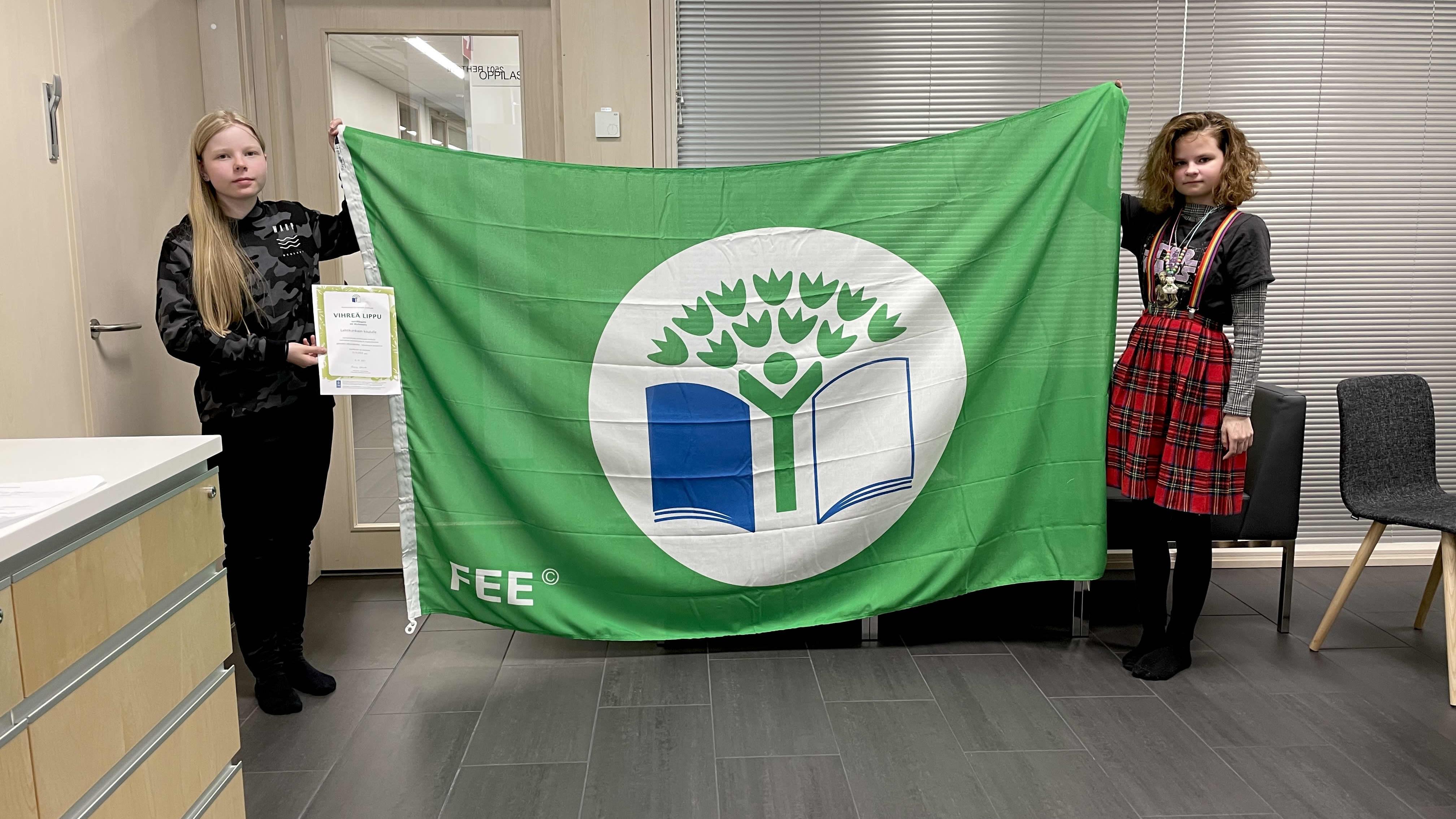 Kaksi tyttöä pitää FEE vihreää lippua